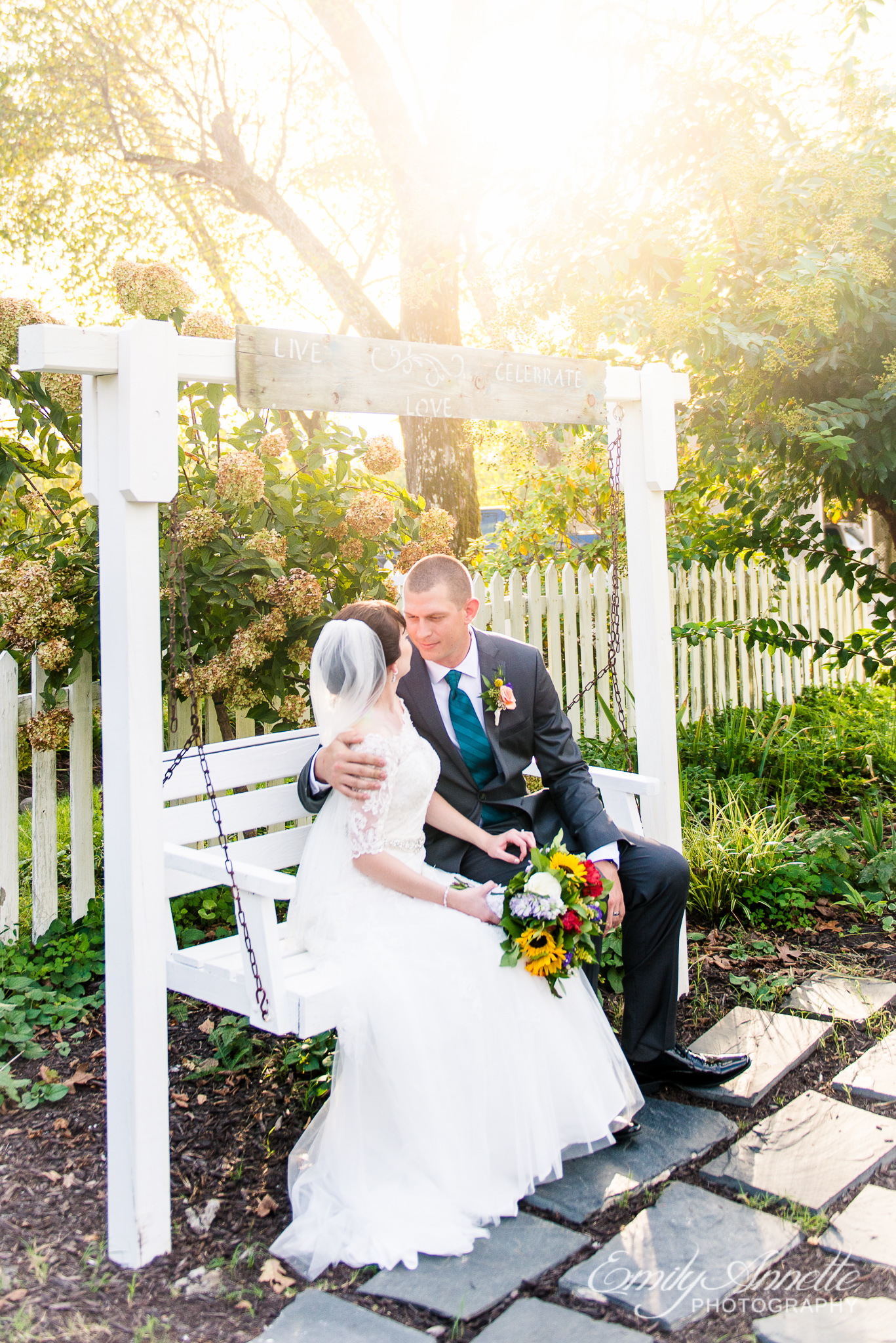 A bride and groom share a quiet moment together on a porch swing during their country wedding at Amber Grove near Richmond, Virginia