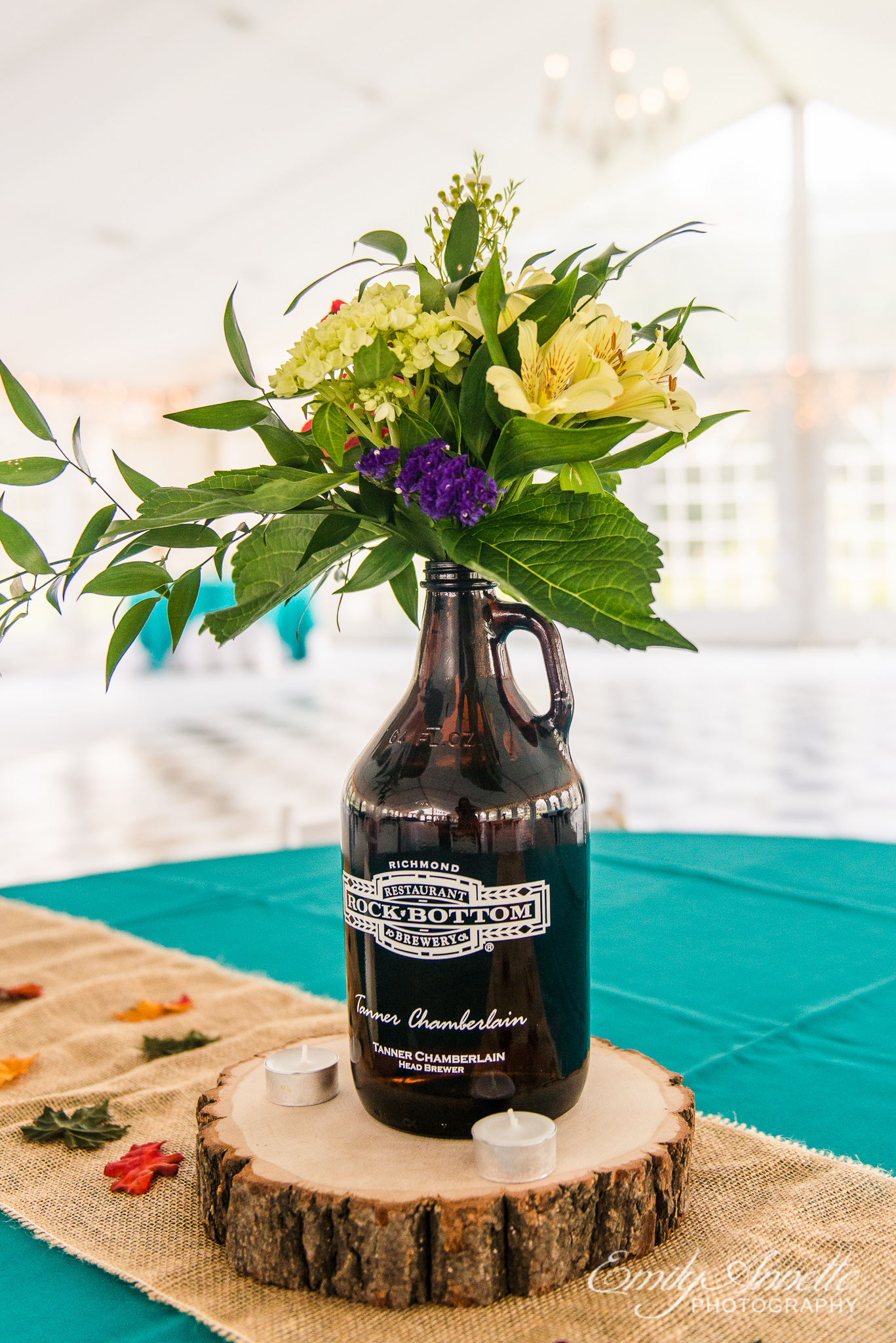 A table decorated with local beer brewery jugs and fall flowers for a country wedding reception at Amber Grove near Richmond, Virginia