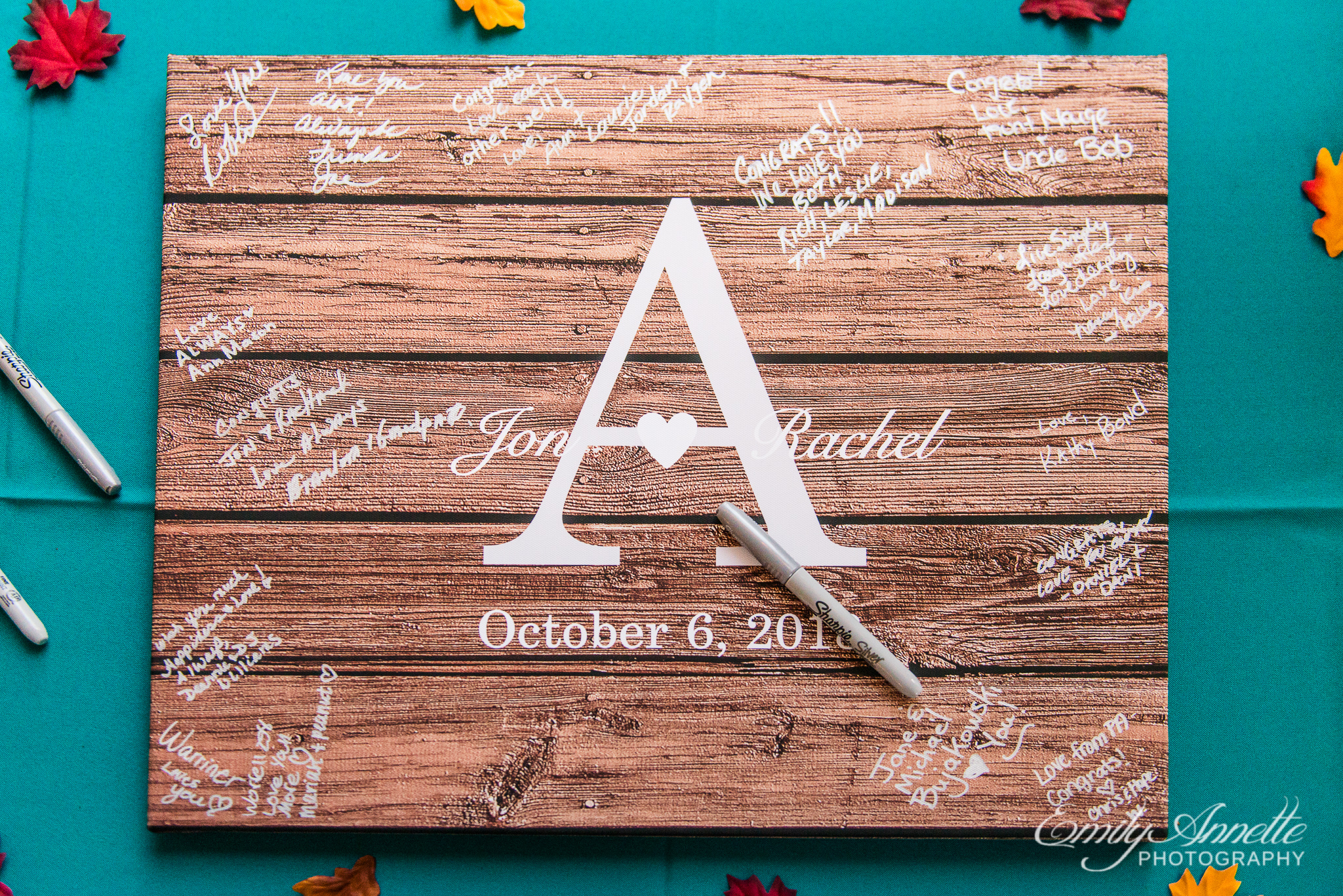 A wooden monogrammed signing board being used as a guest book for a country wedding reception at Amber Grove near Richmond, Virginia
