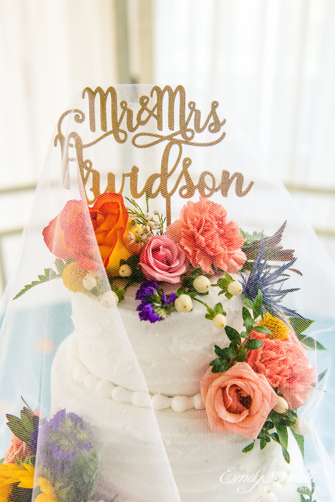 A classic buttercream wedding cake decorated with fall flowers, a personalized topper, and a white veil for a country wedding reception at Amber Grove near Richmond, Virginia