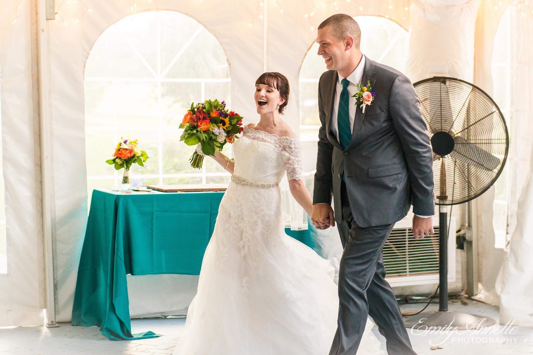 A bride and groom joyfully enter their country wedding reception at Amber Grove near Richmond, Virginia
