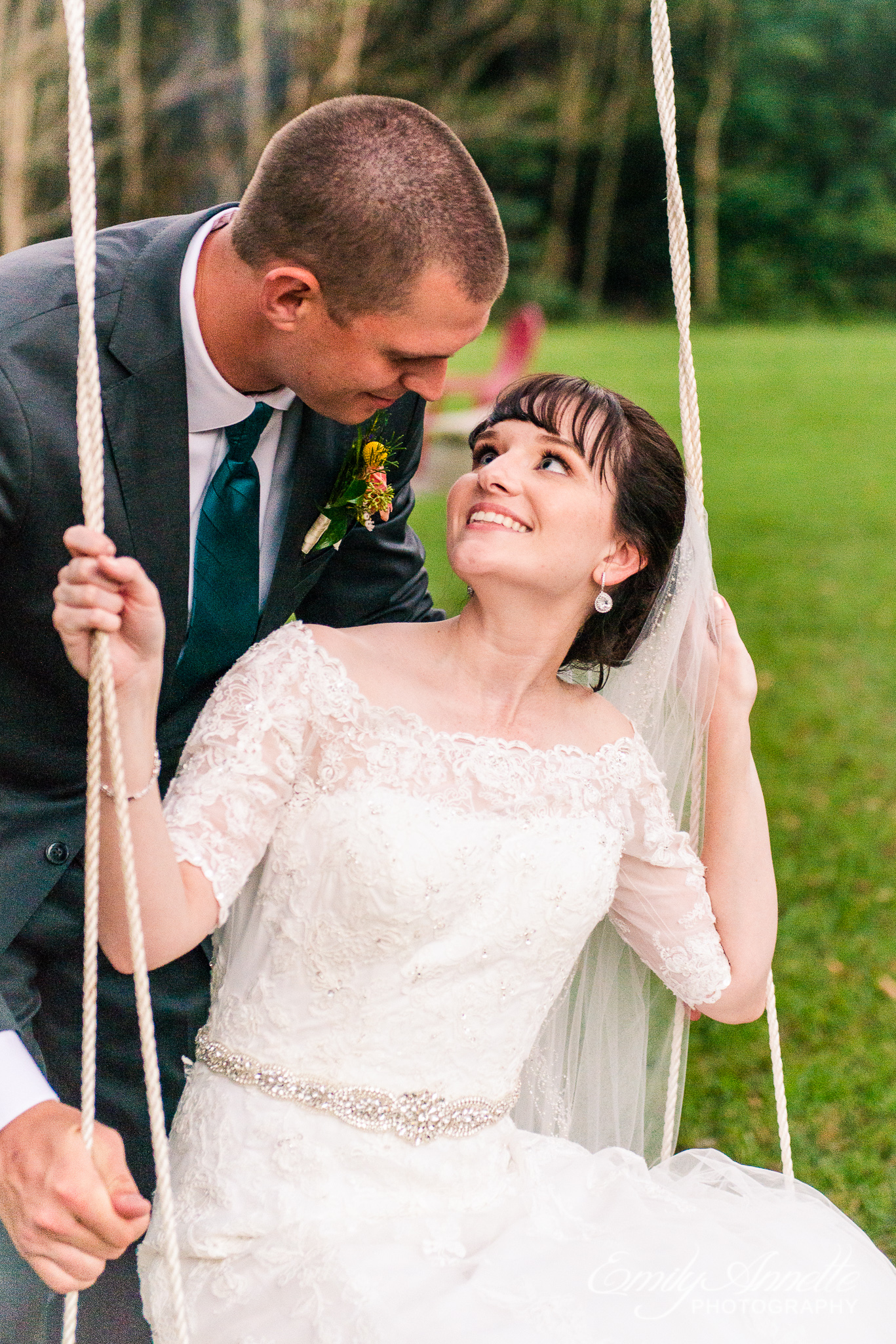 A bride and groom look at each other while enjoying a swing hanging from a tree after their country wedding at Amber Grove near Richmond, Virginia