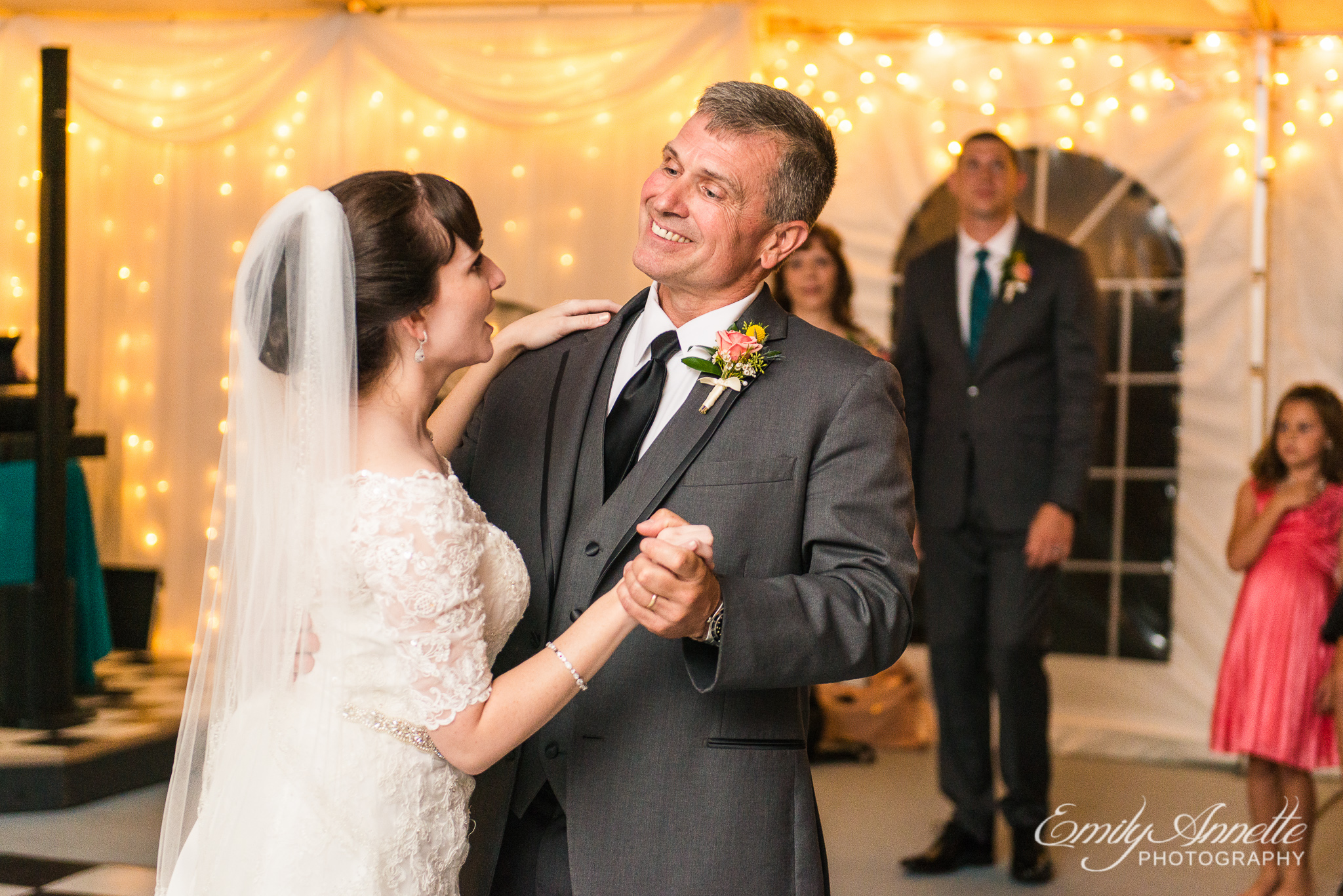 A bride and the father of the bride share their father daughter dance with smiles during a country wedding reception at Amber Grove near Richmond, Virginia