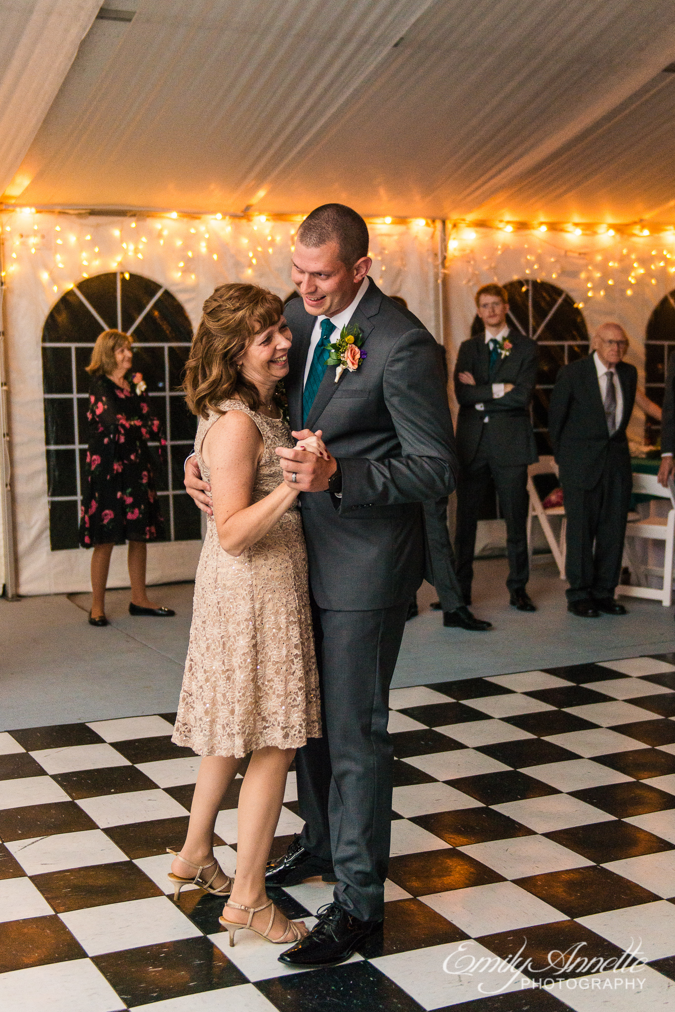 A groom and the mother of the groom share their mother son dance with smiles during a country wedding reception at Amber Grove near Richmond, Virginia