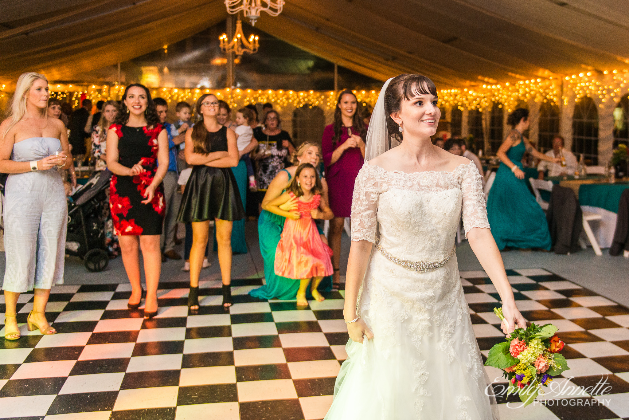 A bride throws her colorful fall bouquet to a group of single ladies during a country wedding reception at Amber Grove near Richmond, Virginia