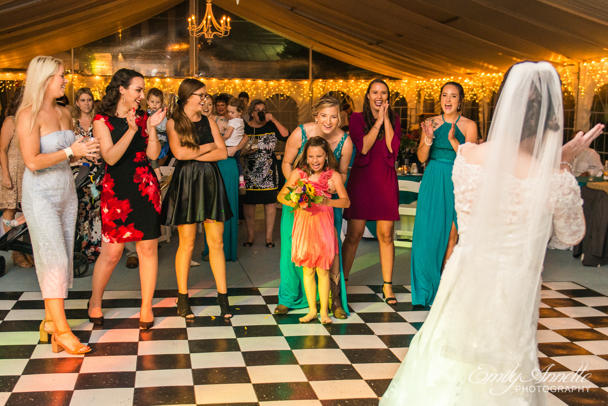 A young girl who caught the bouquet during the bouquet toss of a country wedding reception at Amber Grove near Richmond, Virginia