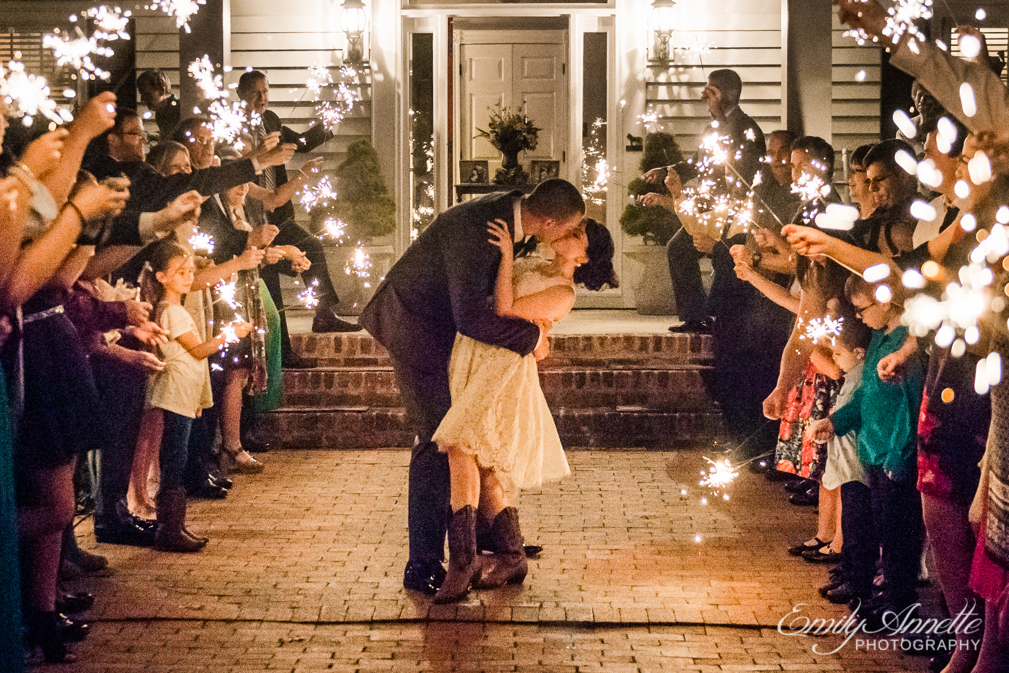 A bride and groom stop for a kiss during their sparkler exit after their country wedding reception at Amber Grove near Richmond, Virginia