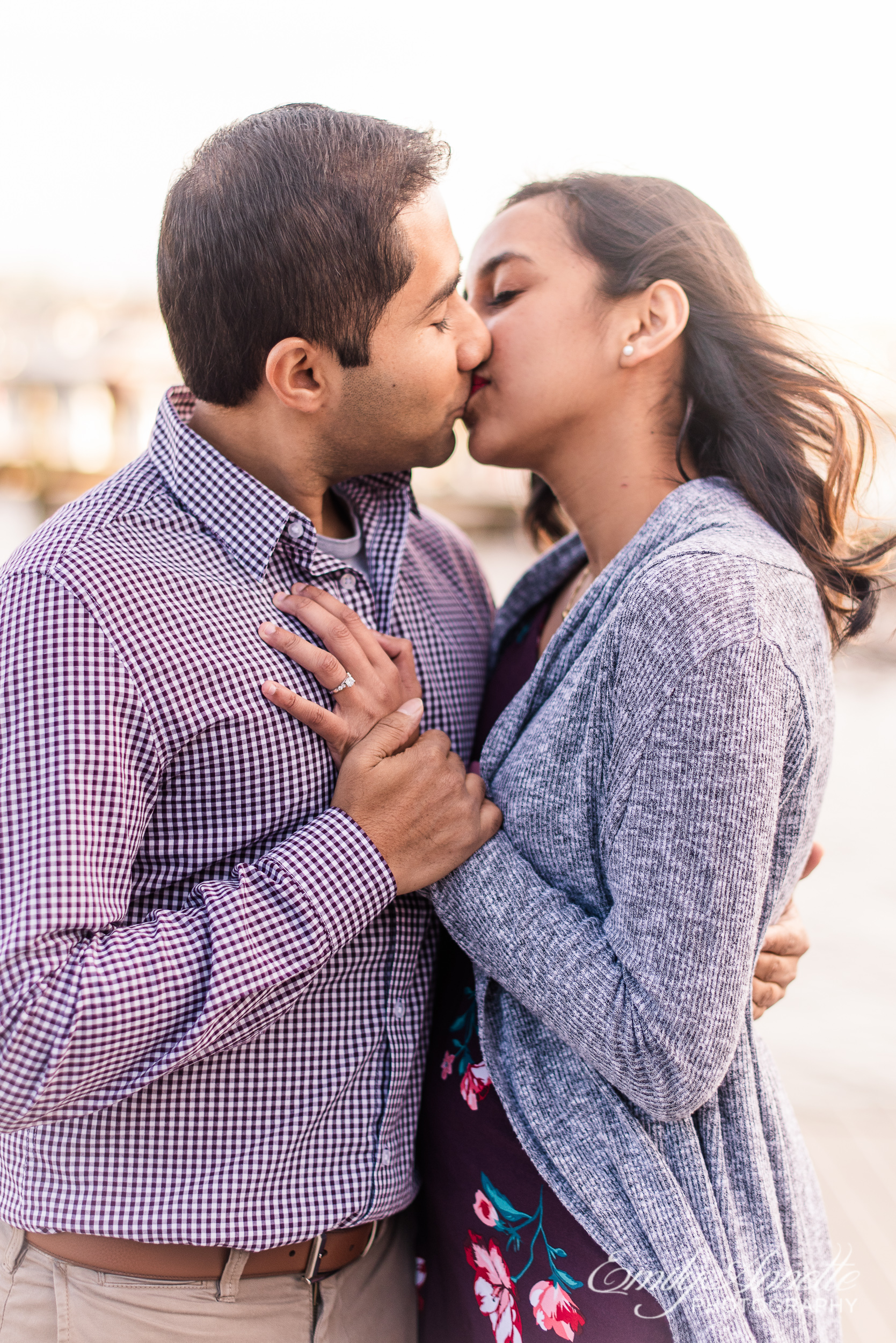 An engaged couple kisses by the Potomac River docks in Old Town Alexandria Virginia for an engagement session