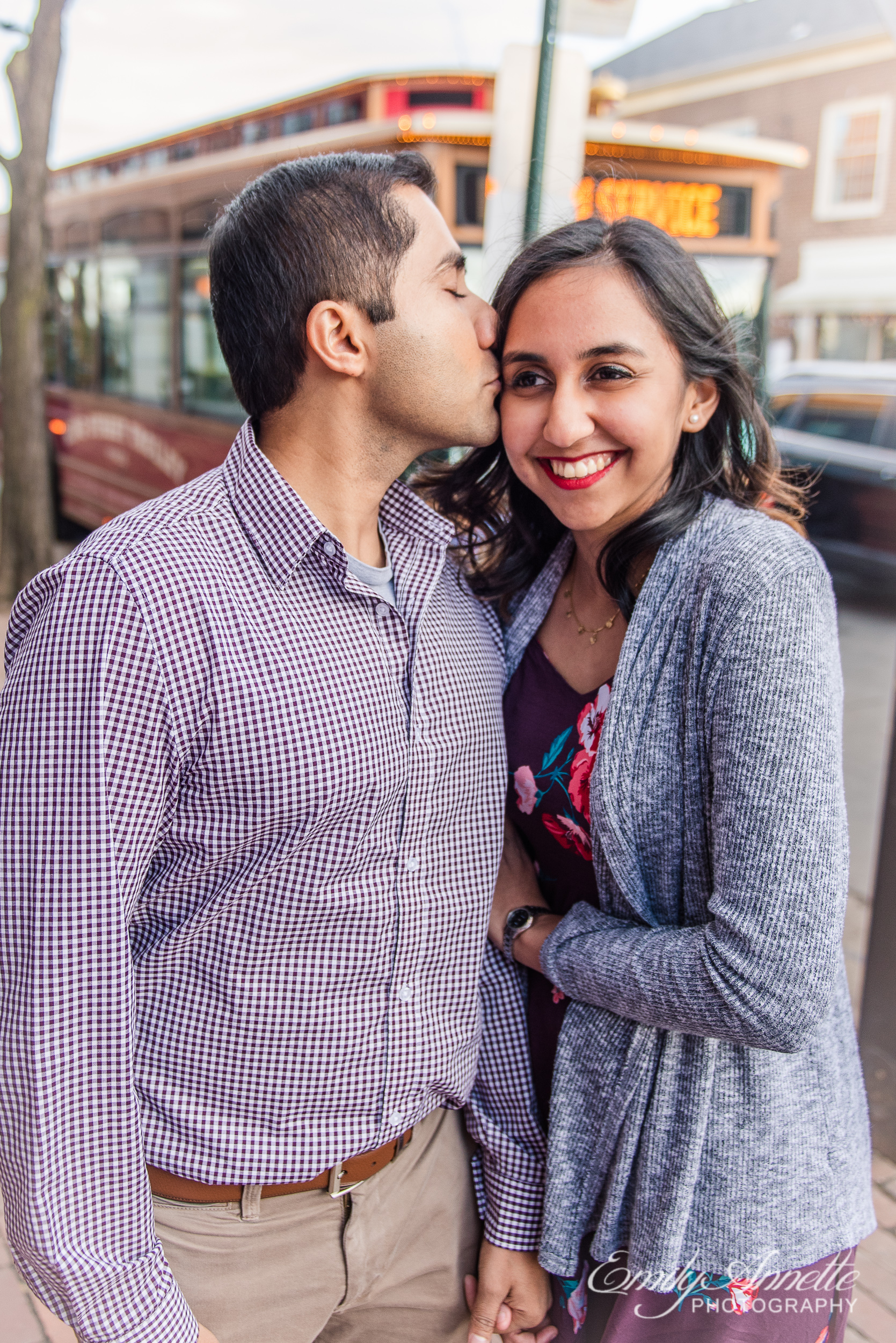 An engaged couple poses in Old Town Alexandria Virginia with an iconic King Street trolley behind them for an engagement session