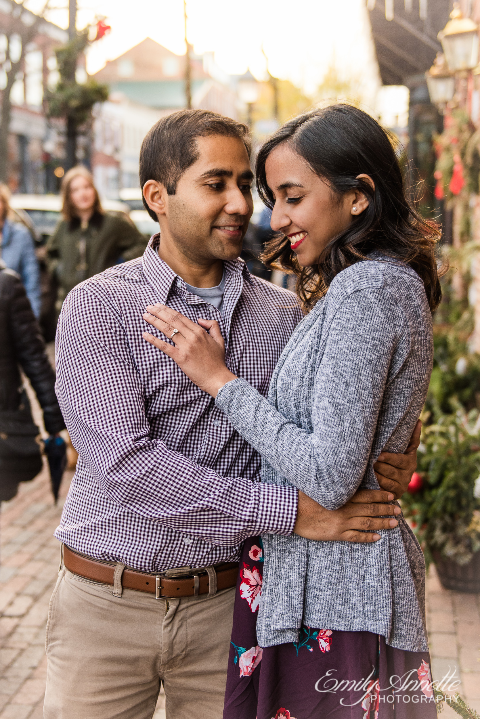 An engaged couple poses along King Street in Old Town Alexandria Virginia for an engagement session