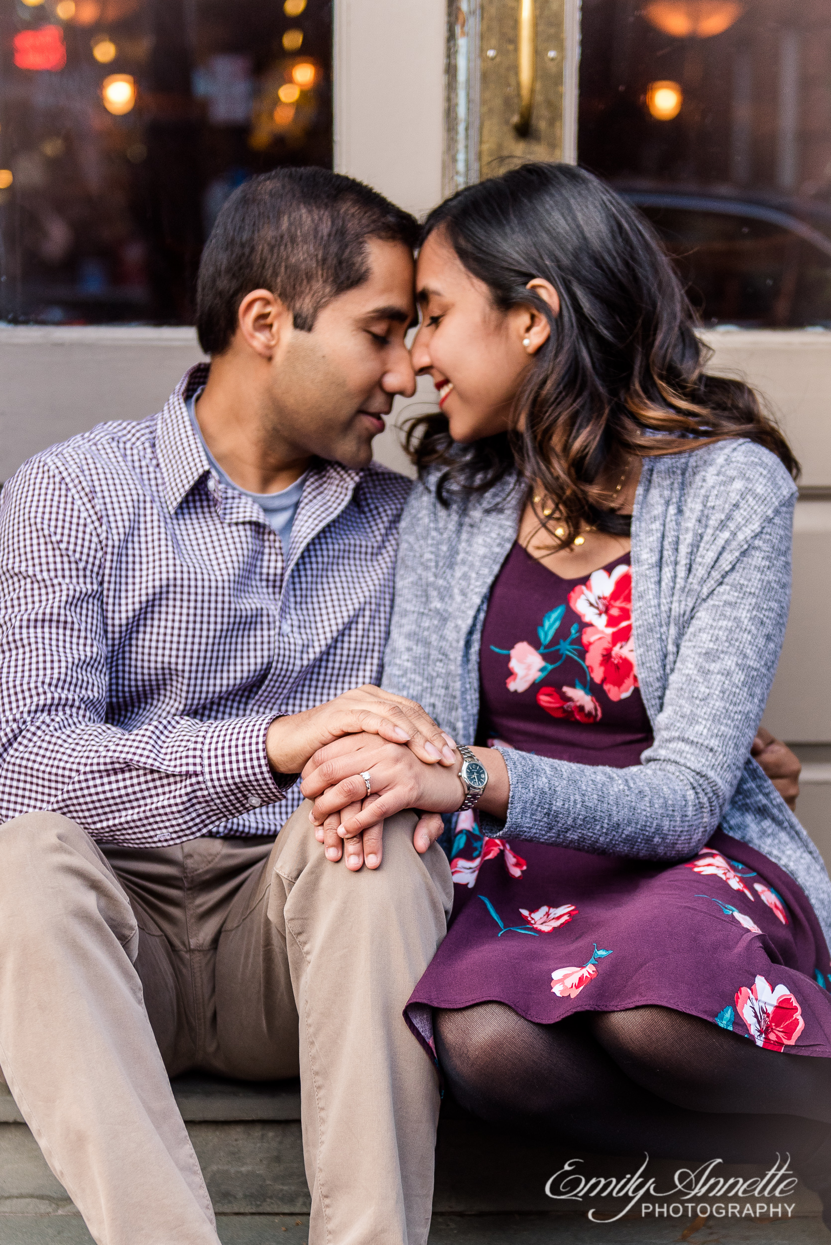 An engaged couple sits along King Street in Old Town Alexandria Virginia for an engagement session