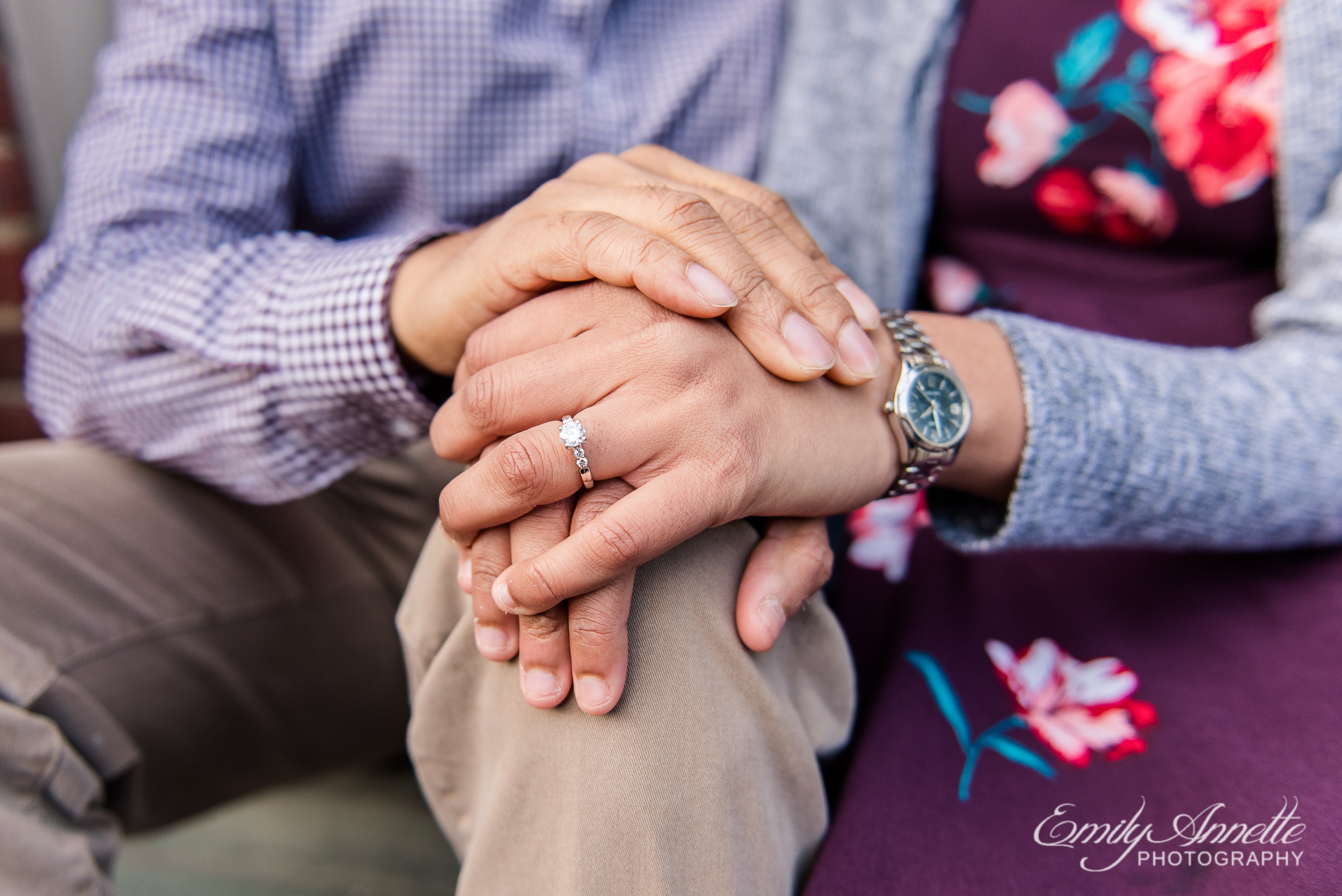 A close up of the engagement ring of a young couple sitting along King Street in Old Town Alexandria Virginia for an engagement session