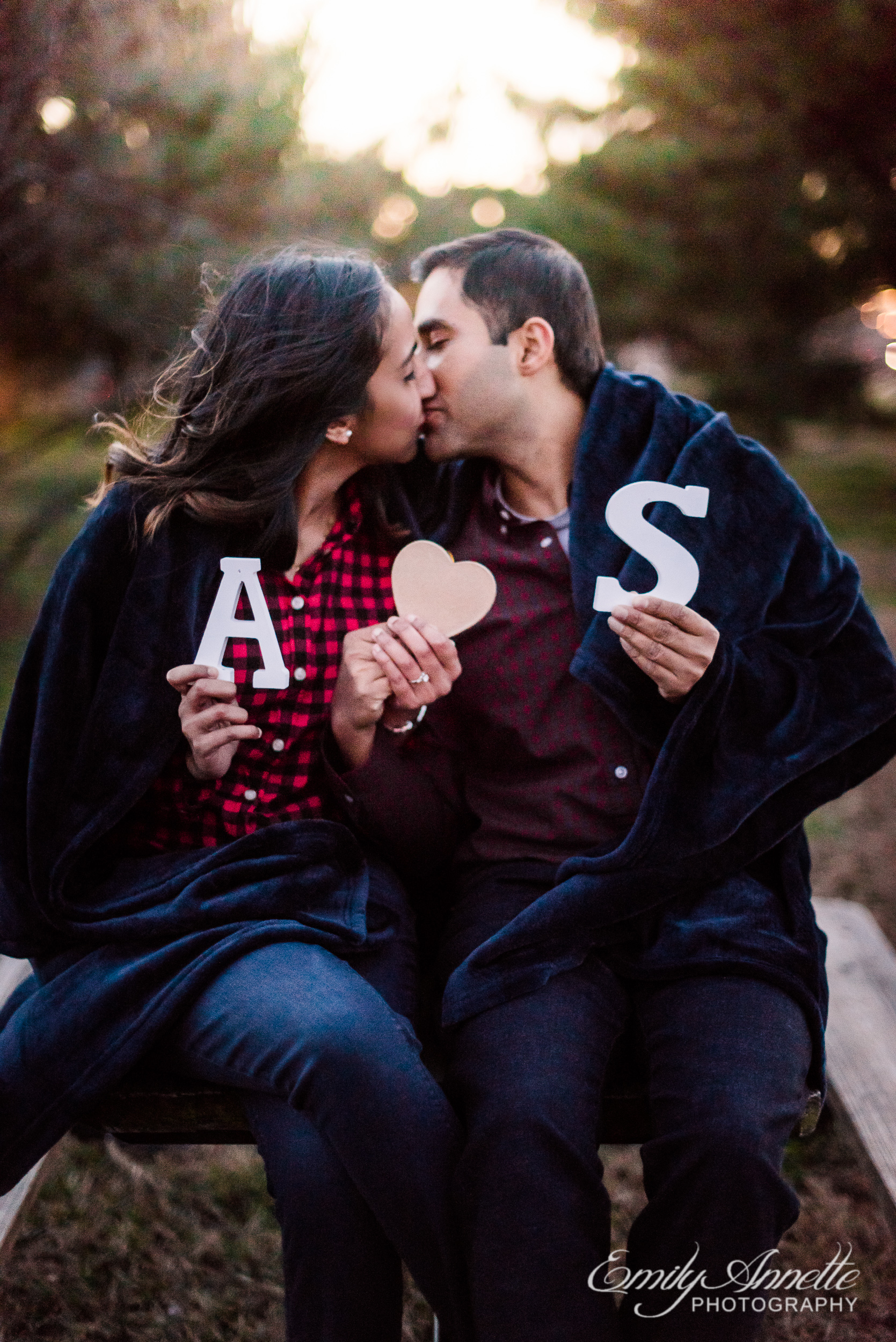 An engaged couple holds up cutouts of their initials while sitting on a picnic table at Gravelly Point Park in Arlington Virginia for an engagement session