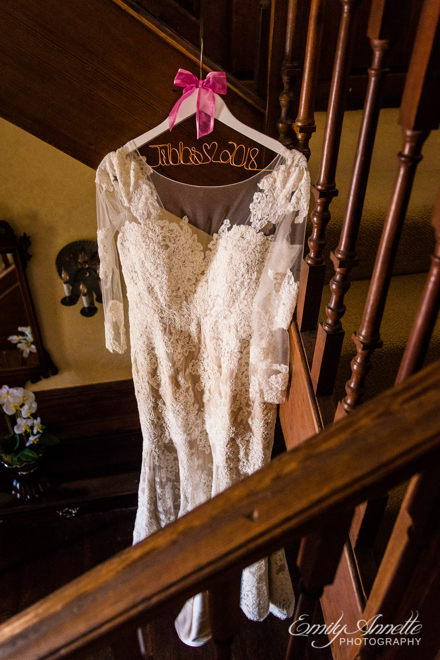 A lace wedding dress with sleeves hanging from the stairs while the bride is getting ready at Willow Oaks Country Club in Richmond, Virginia