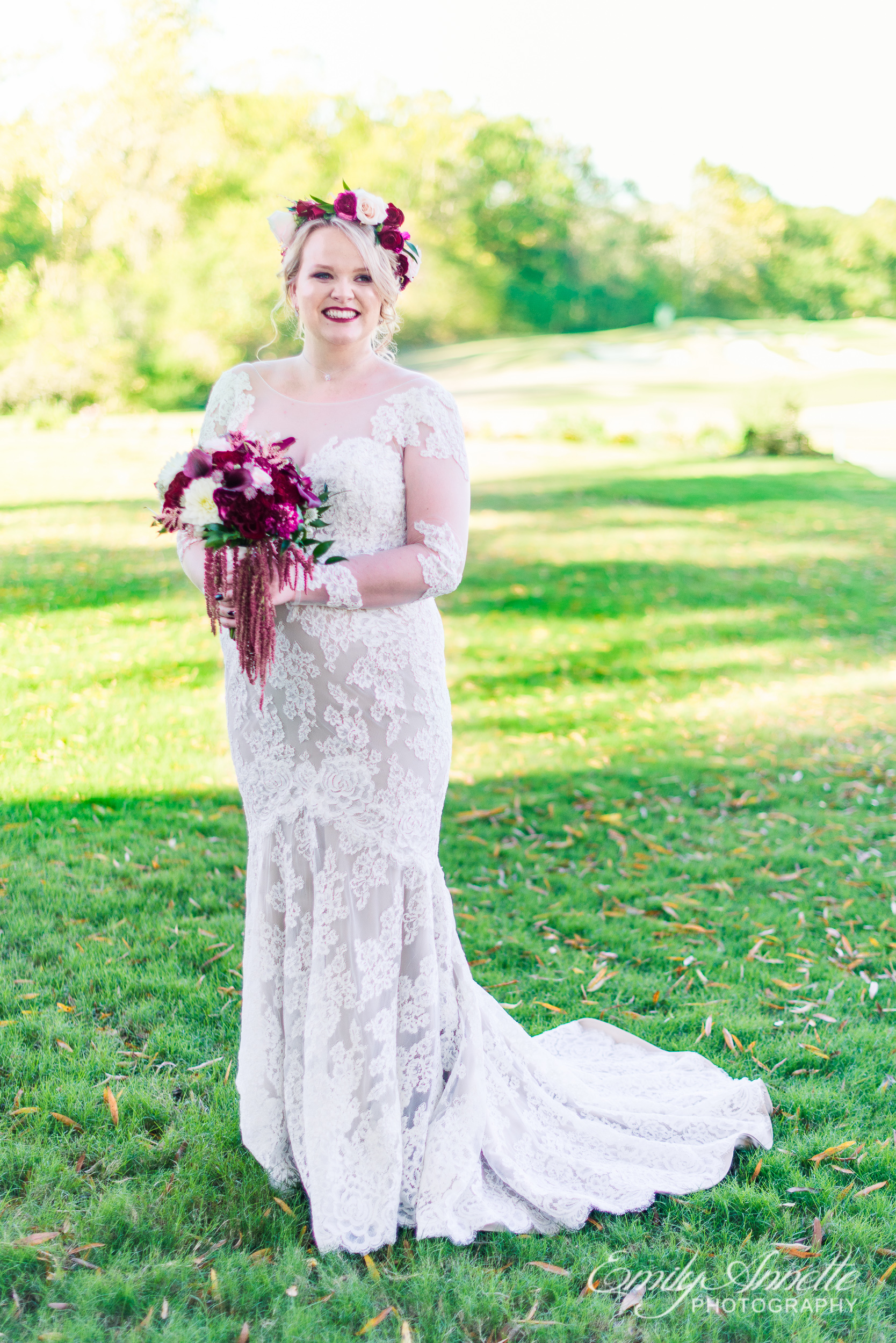 A bride wearing a lace wedding dress with sleeves and a flower crown holding her bridal bouquet on the golf course at Willow Oaks Country Club in Richmond, Virginia