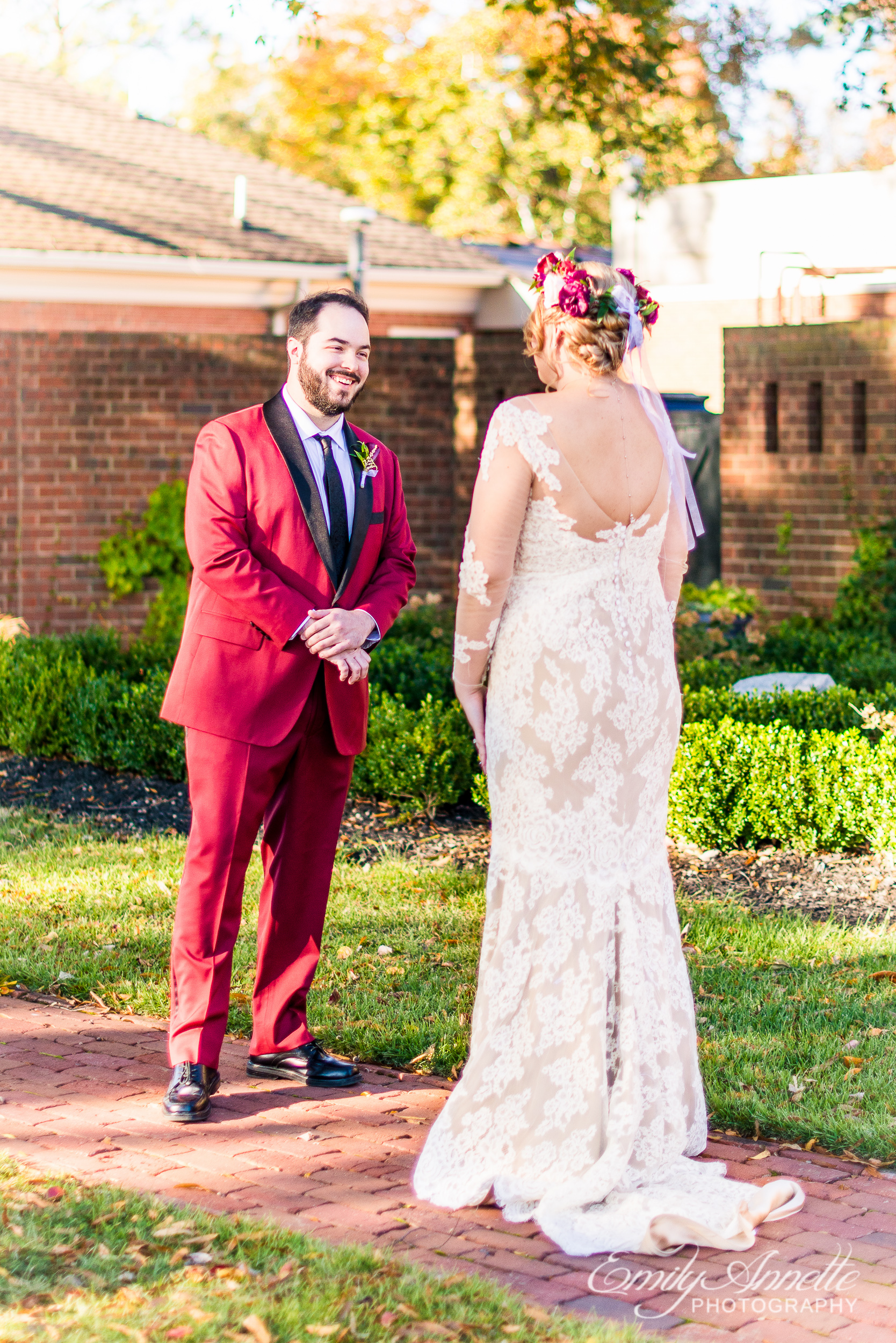A groom in a red suit excited as he sees his bride for the first time for their first look before their wedding ceremony at Willow Oaks Country Club in Richmond, Virginia