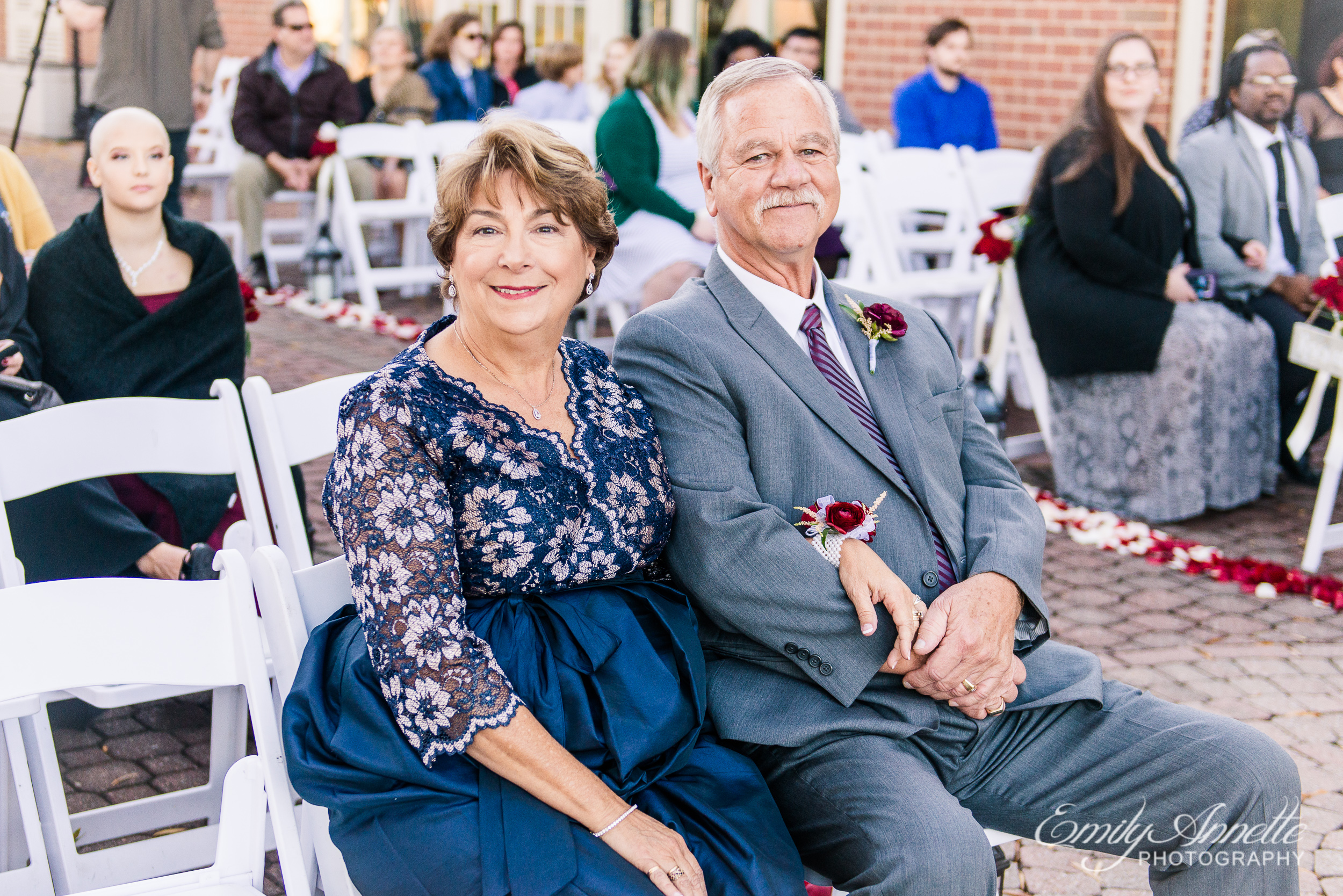 The parents of the groom sitting in the front row before the wedding ceremony at Willow Oaks Country Club in Richmond, Virginia