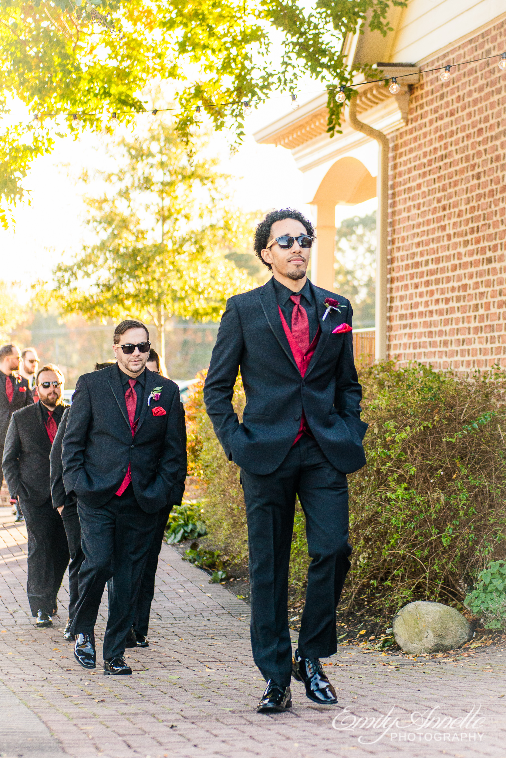 Groomsmen in sunglasses wearing black and red suits walking into the wedding ceremony at Willow Oaks Country Club in Richmond, Virginia