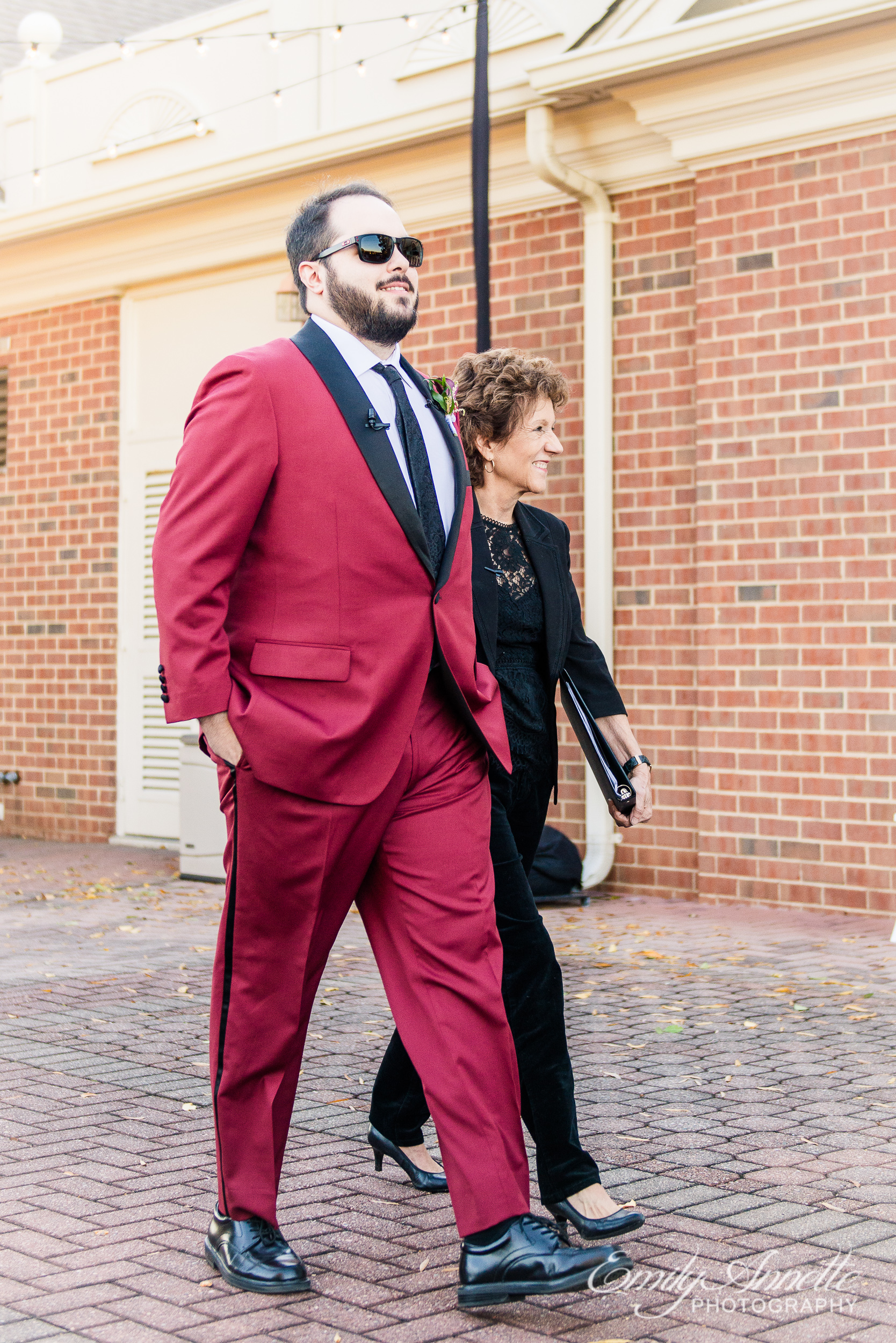 A groom in a red suit and sunglasses and the officiant walking into the wedding ceremony at Willow Oaks Country Club in Richmond, Virginia