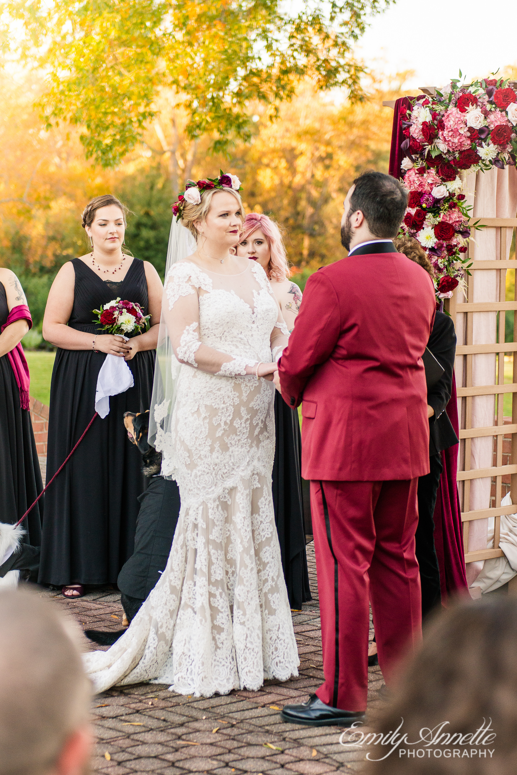 A bride looking at her groom while holding hands during an outdoor wedding ceremony at Willow Oaks Country Club in Richmond, Virginia
