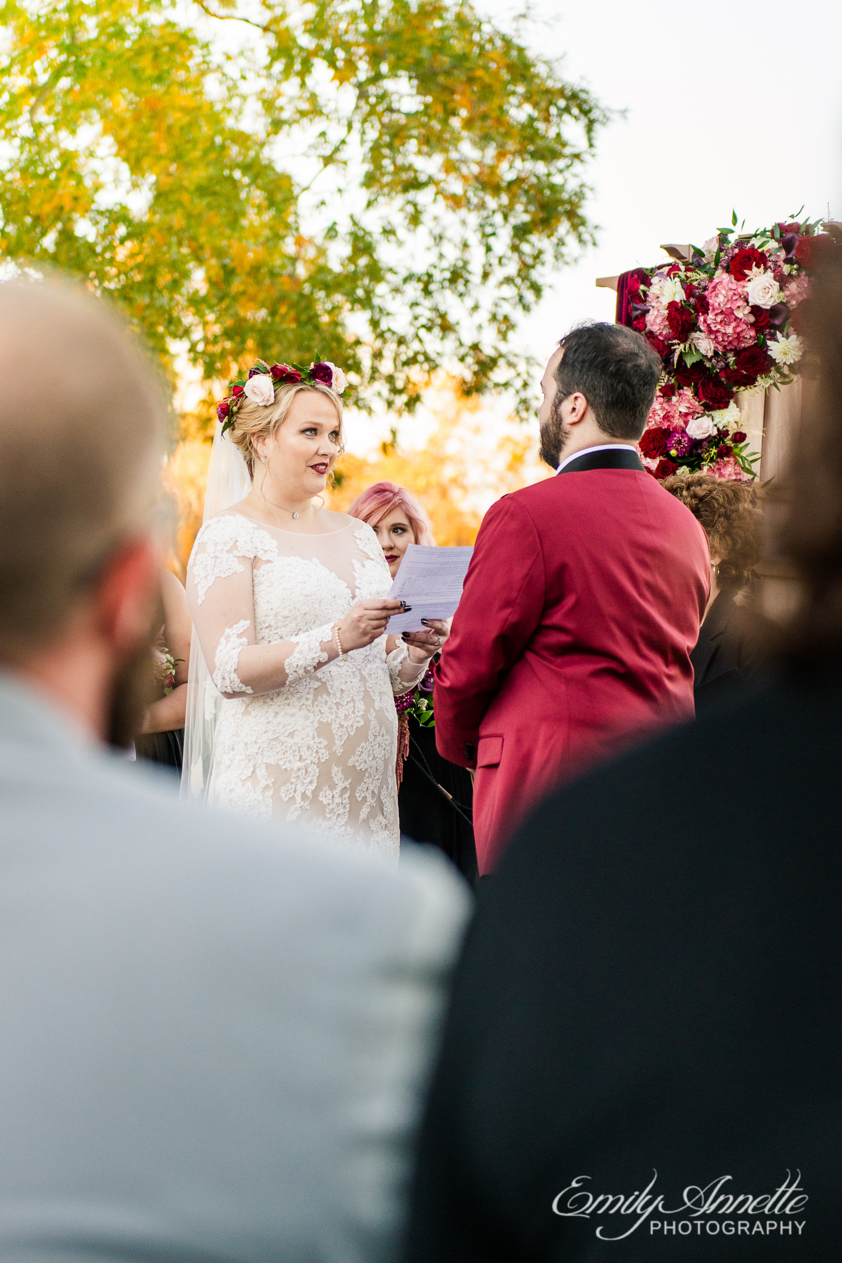 View over the shoulders of guests of a bride reading her vows to her groom at the altar during an outdoor wedding ceremony at Willow Oaks Country Club in Richmond, Virginia