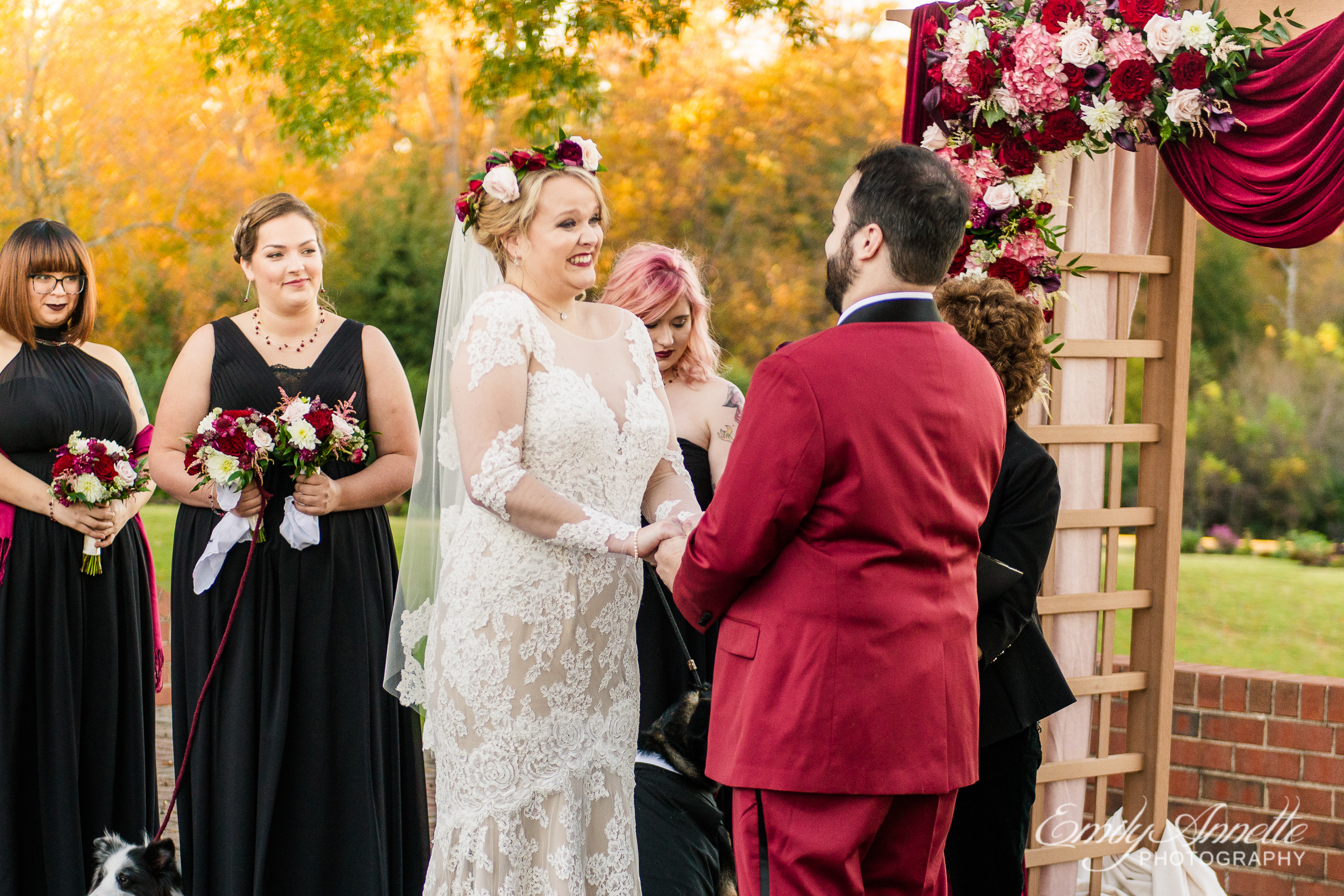 A bride smiles and laughs at her groom while holding his hand at the altar during an outdoor wedding ceremony at Willow Oaks Country Club in Richmond, Virginia