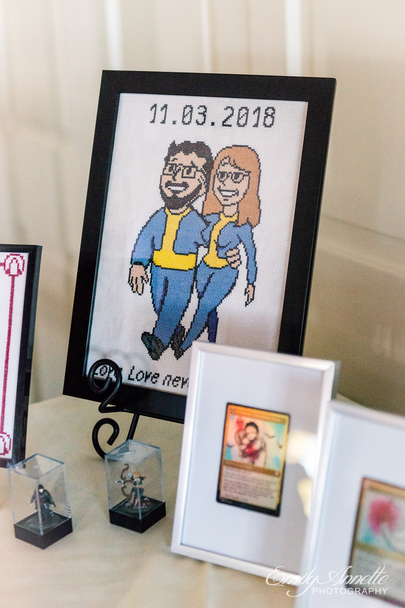 A cross stitch portrait of the bride and groom as characters from Fallout at a wedding reception at Willow Oaks Country Club in Richmond, Virginia