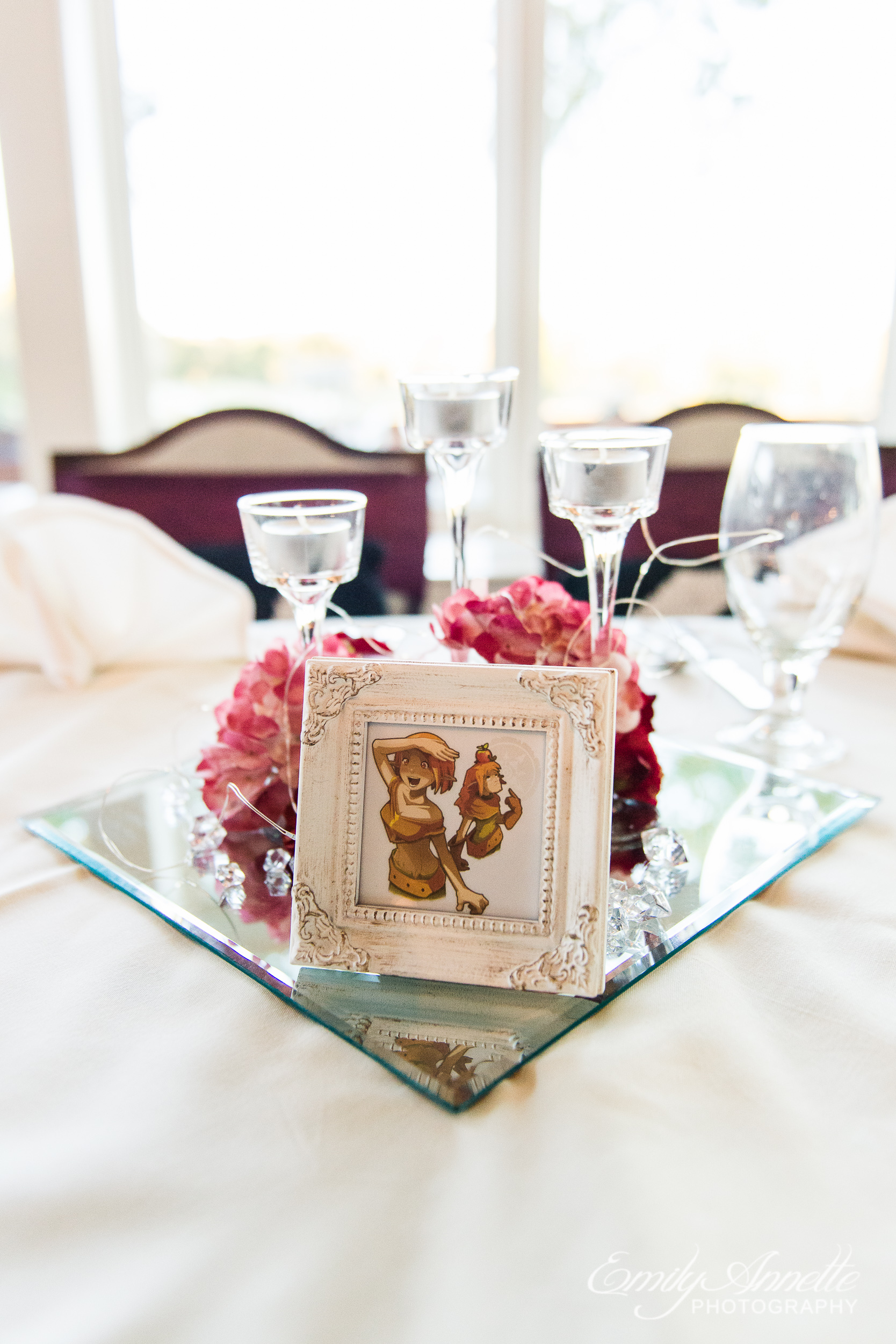 A table centerpiece with flowers, candles, and a framed video game reference as a table number at a wedding reception at Willow Oaks Country Club in Richmond, Virginia