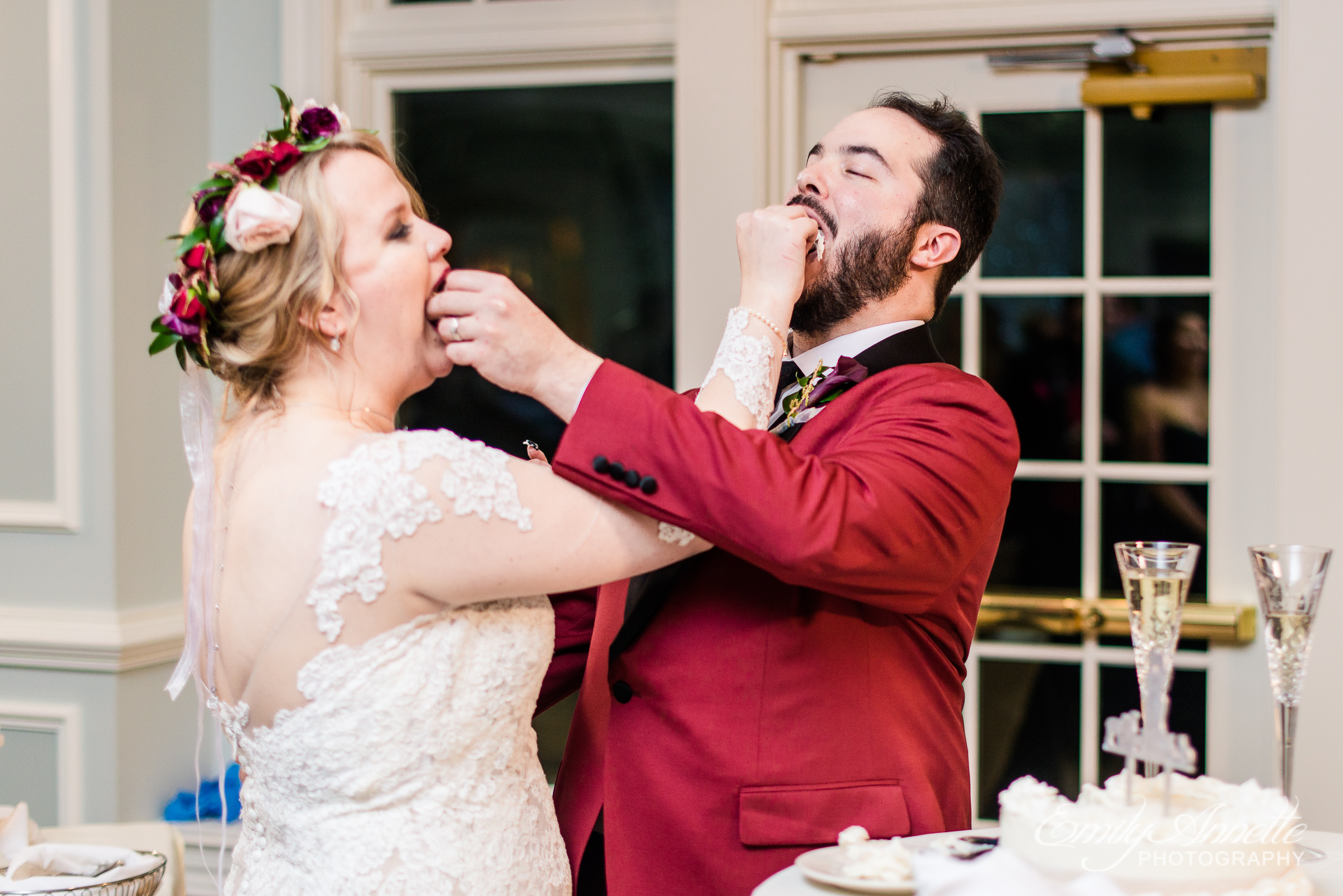 A bride and groom feed each other cake by hand during a wedding reception at Willow Oaks Country Club in Richmond, Virginia