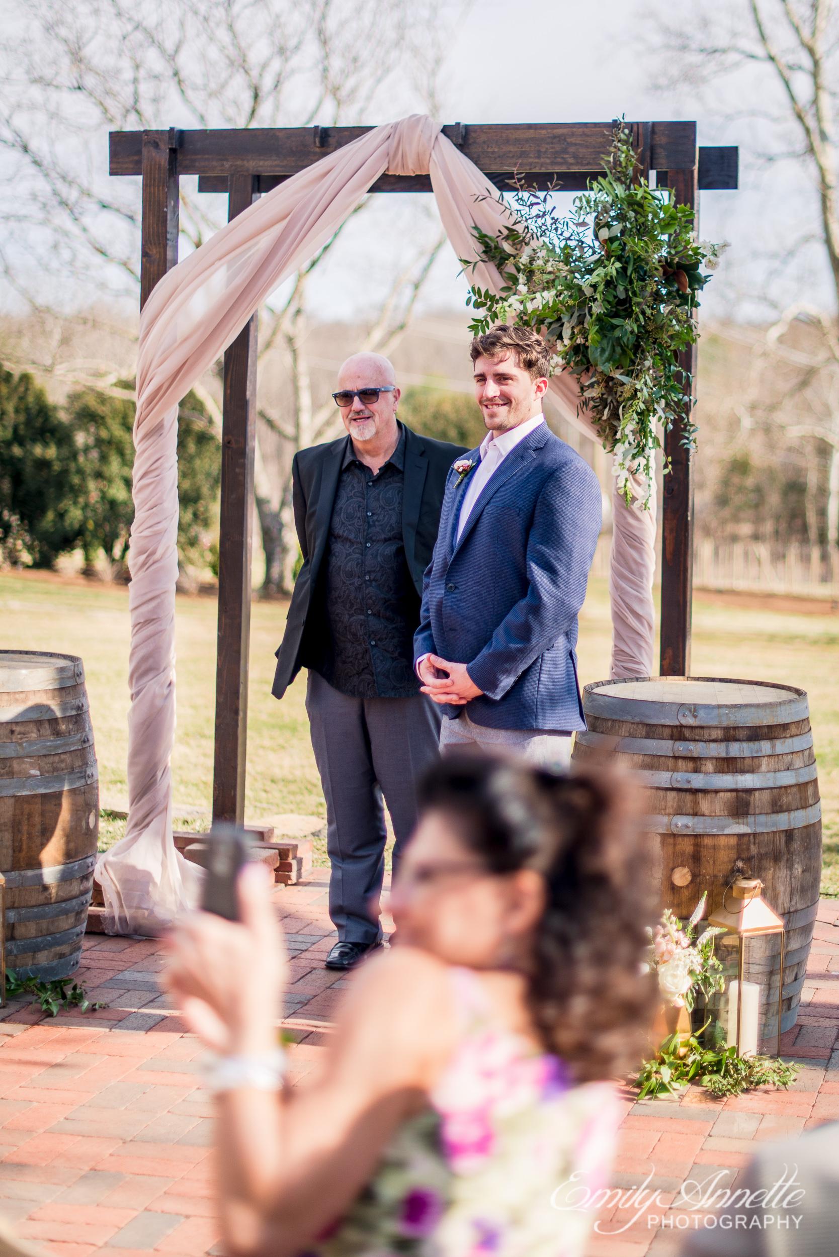 A groom seeing his bride walk down the aisle during their spring wedding at Fleetwood Farm Winery in Leesburg, Virginia