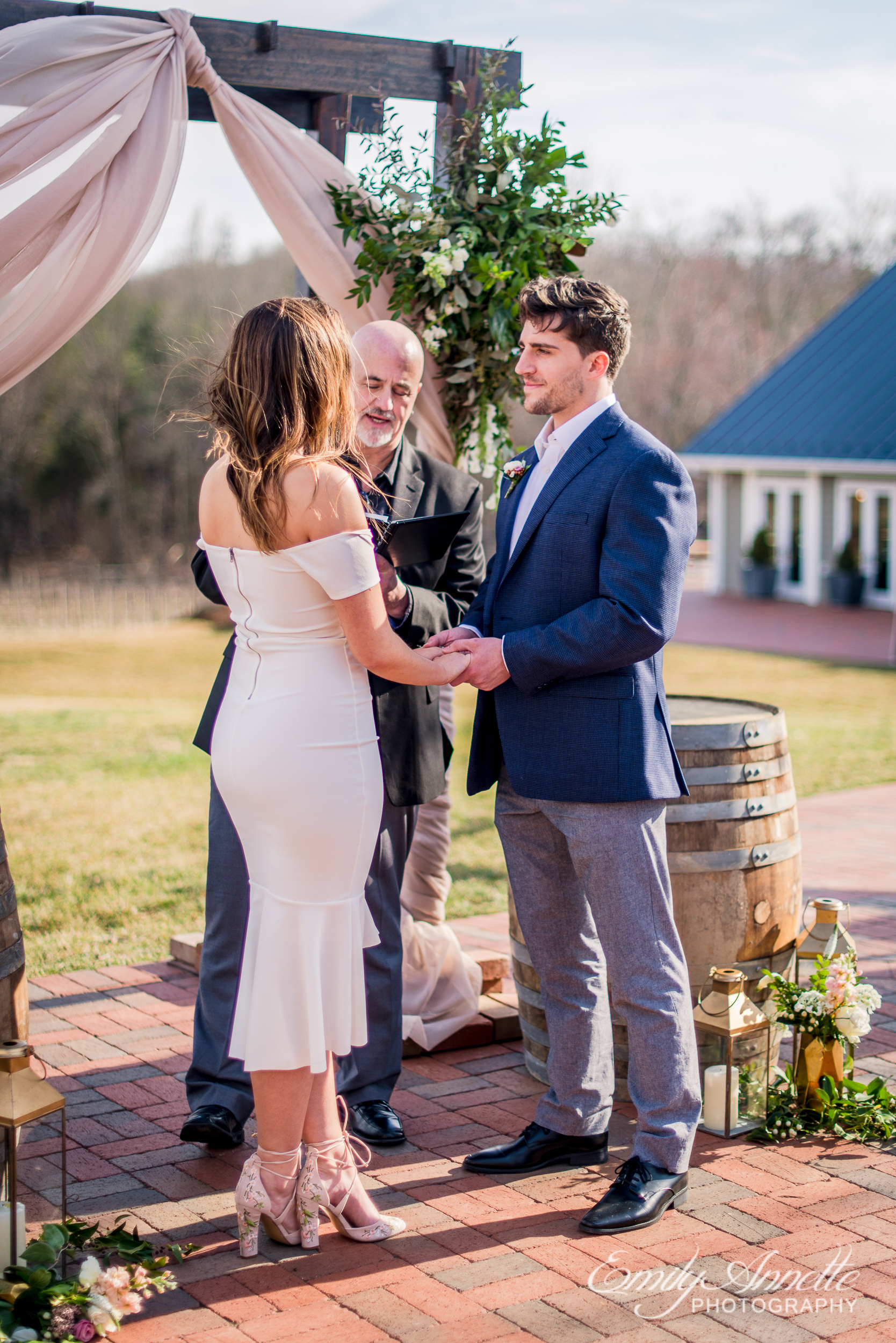 The bride and groom stand at the altar as the groom looks at his bride during their wedding ceremony at Fleetwood Farm Winery in Leesburg, Virginia