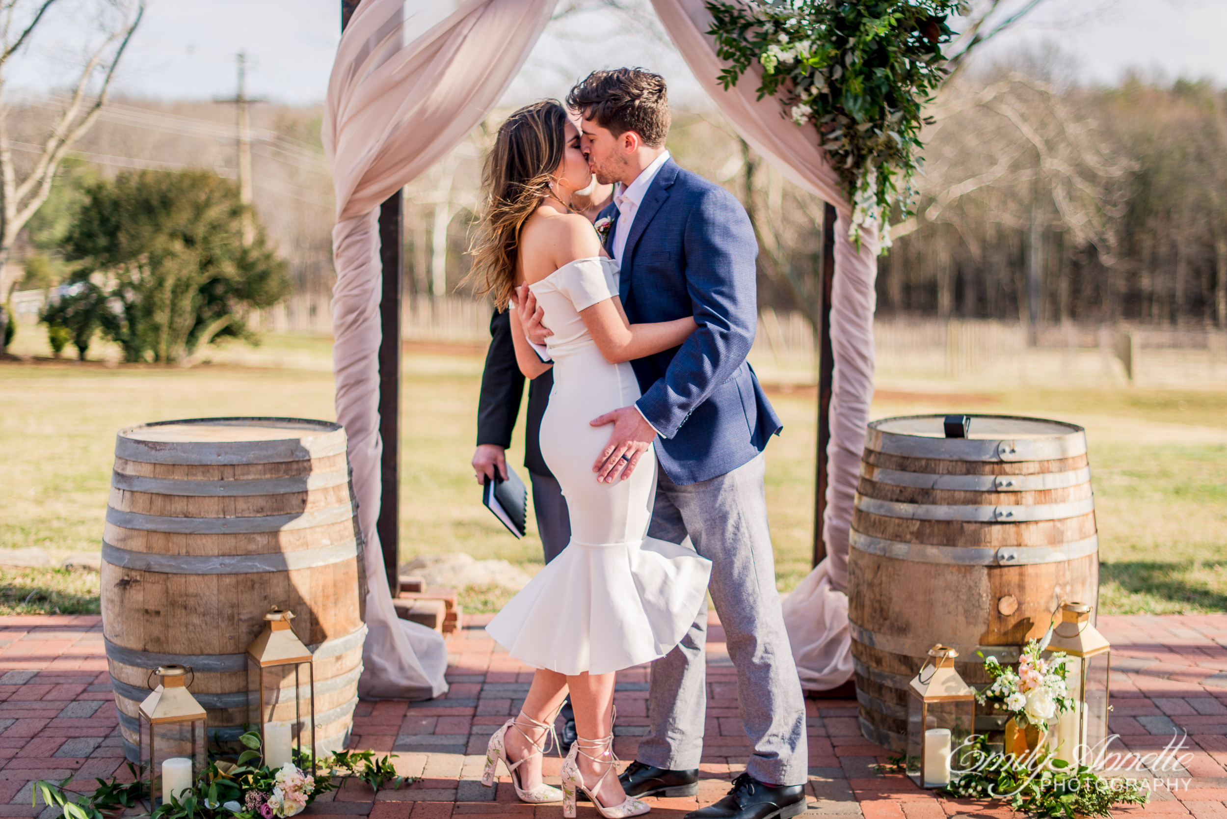 The first kiss as husband and wife during their wedding ceremony at Fleetwood Farm Winery in Leesburg, Virginia