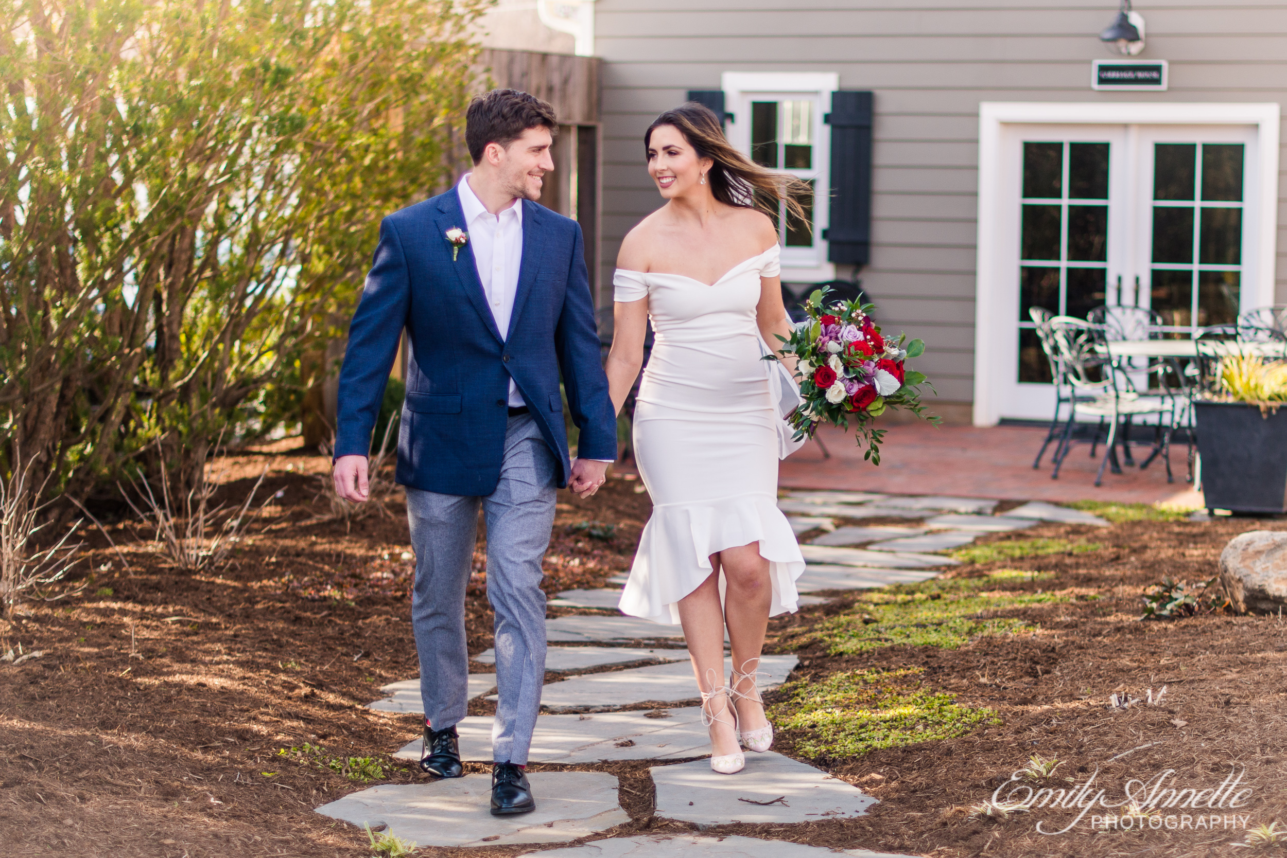 A bride and groom hold hands as they walk together on their wedding day at Fleetwood Farm Winery in Leesburg, Virginia