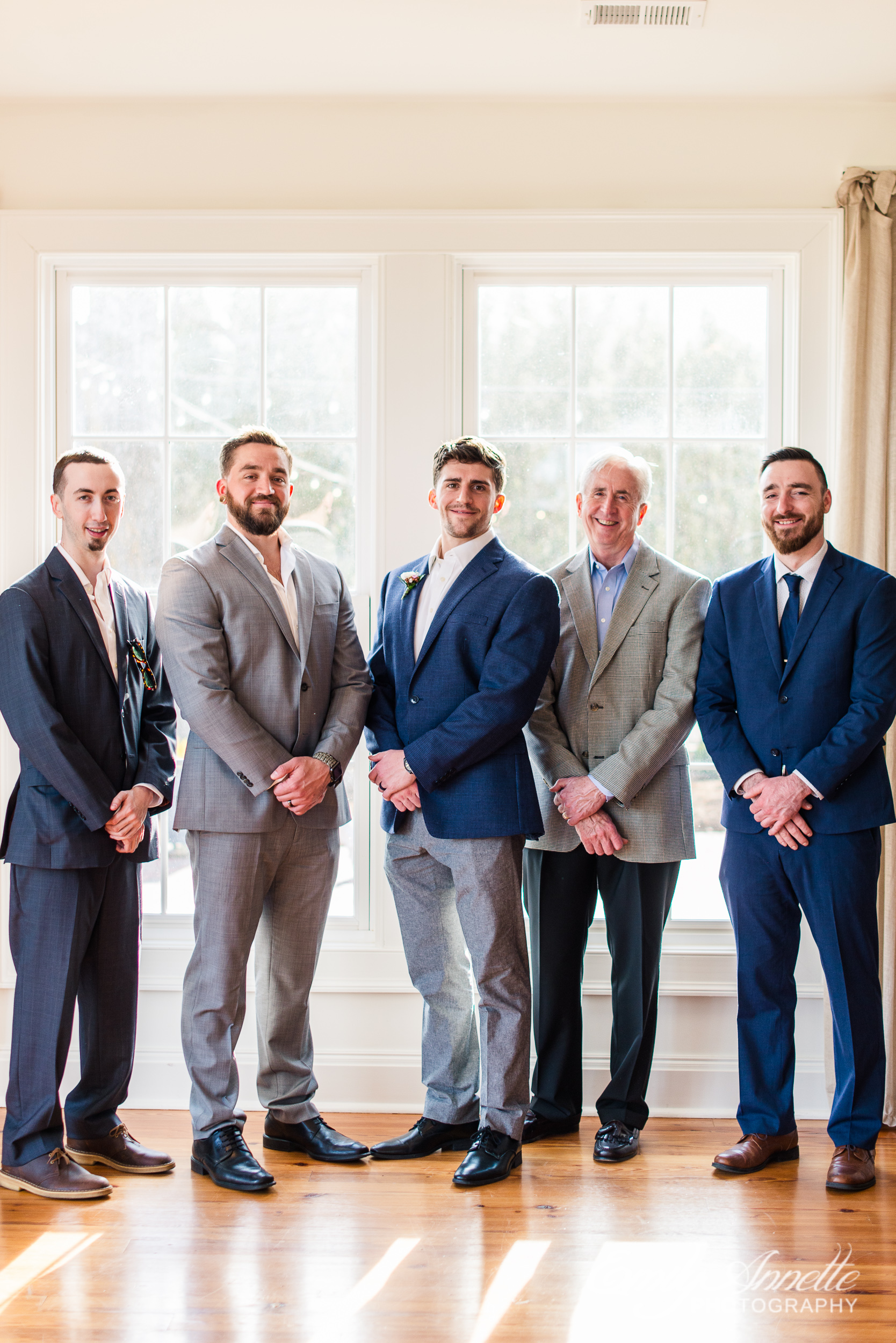 A portrait by the window of all the men at a small wedding at Fleetwood Farm Winery in Leesburg, Virginia