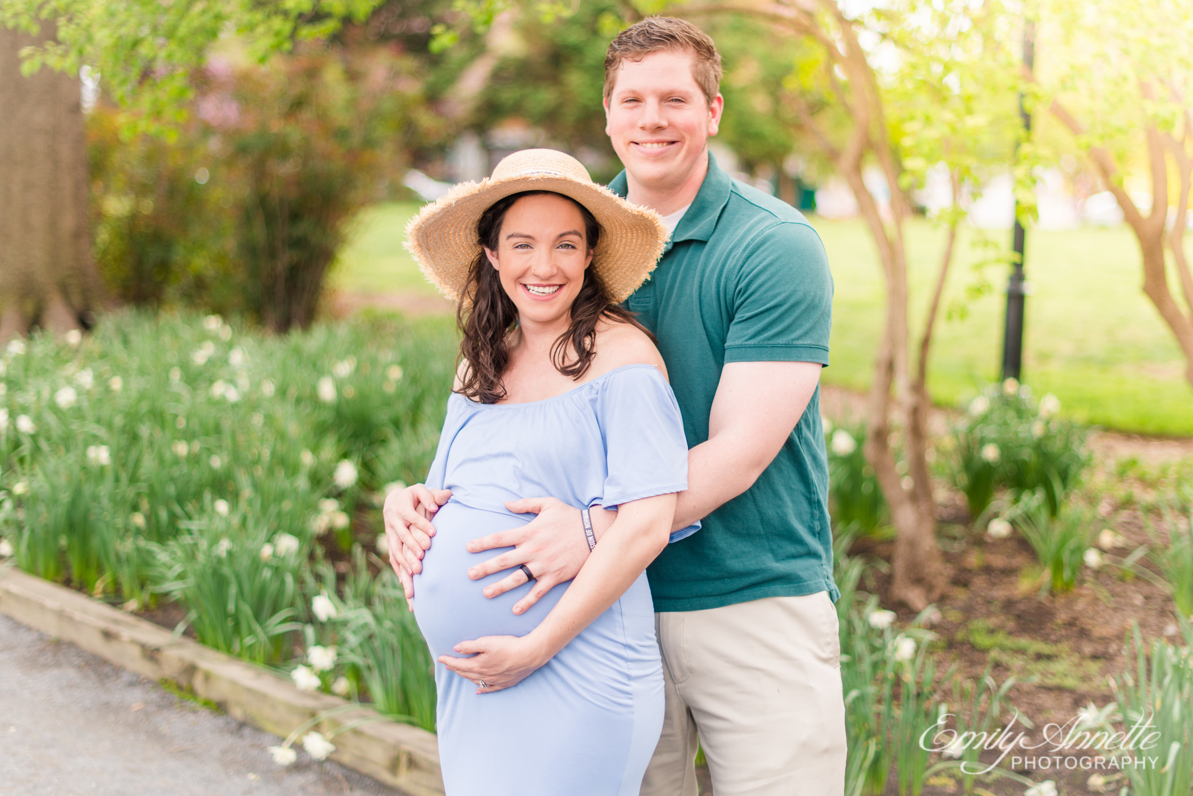A pregnant woman poses with her husband for spring maternity photos in Old Town Alexandria wearing a romantic blue dress