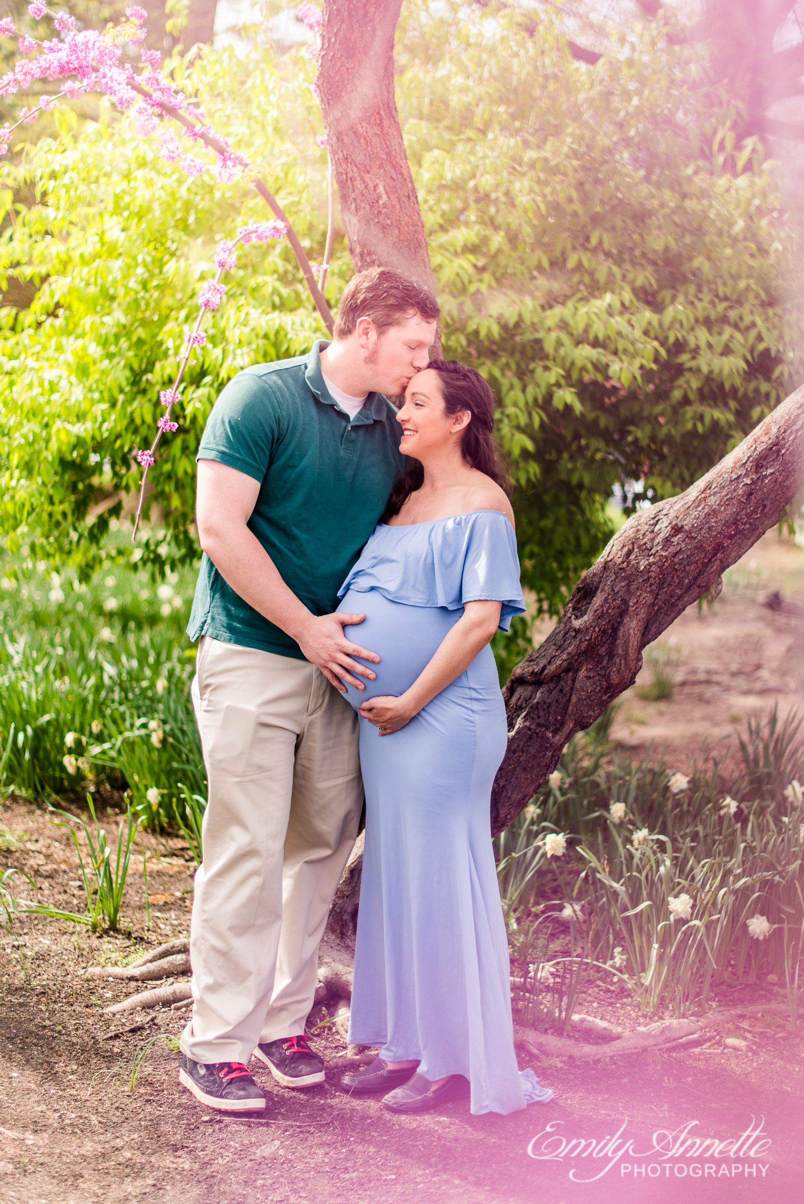 A pregnant woman poses with her husband for spring maternity photos at Waterfront Park in Old Town Alexandria wearing a romantic blue dress