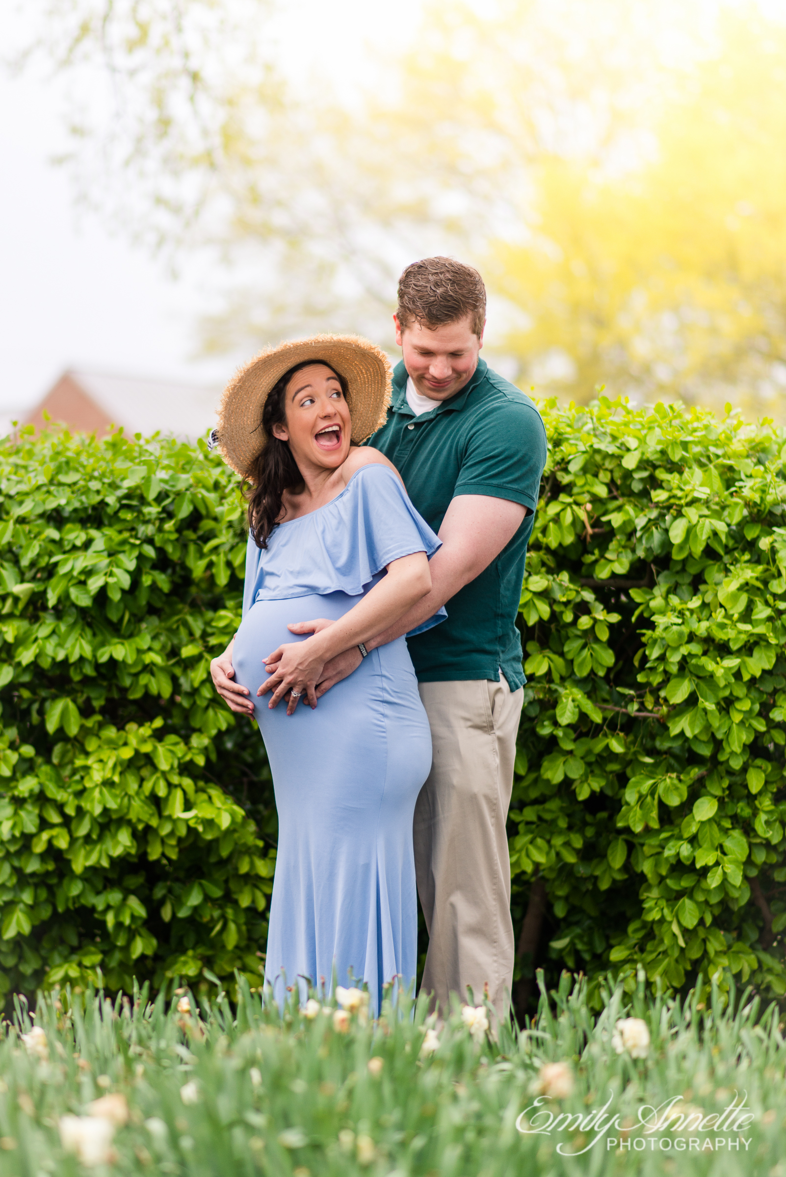 A pregnant woman poses for spring maternity photos at Waterfront Park in Old Town Alexandria wearing a romantic blue dress