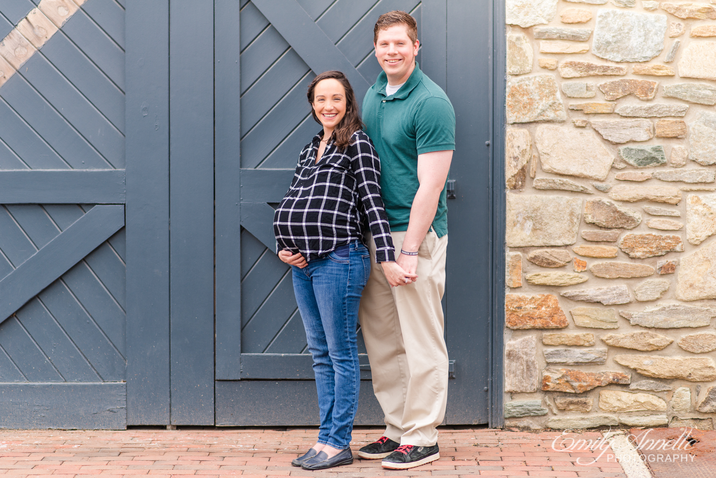 A pregnant woman poses with her husband for maternity photos in Old Town Alexandria wearing a fun casual shirt and jeans