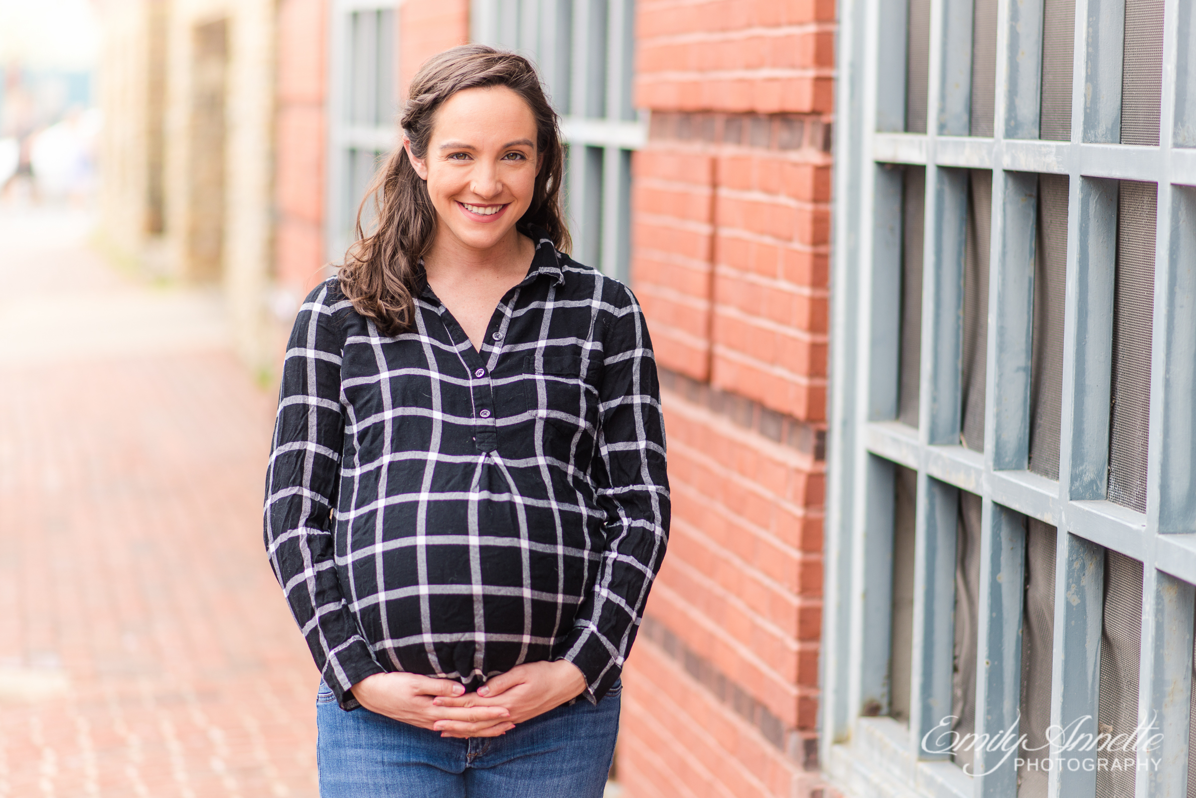 A pregnant woman poses for maternity photos in Old Town Alexandria wearing a fun casual shirt and jeans