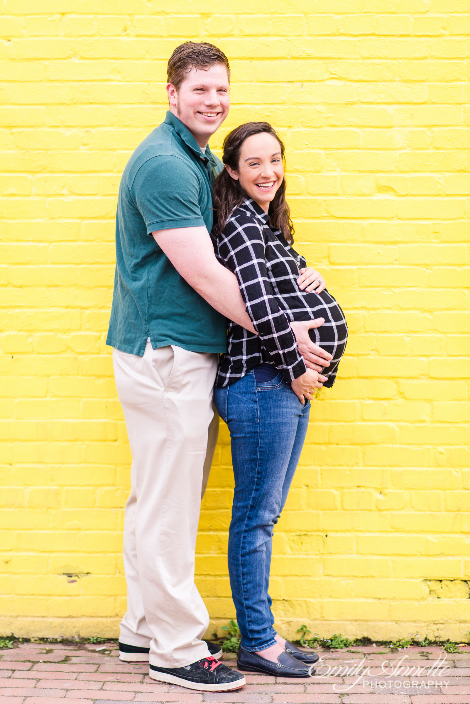 A pregnant woman poses with her husband for urban modern maternity photos in front of a bright yellow wall in Old Town Alexandria wearing a fun casual shirt and jeans