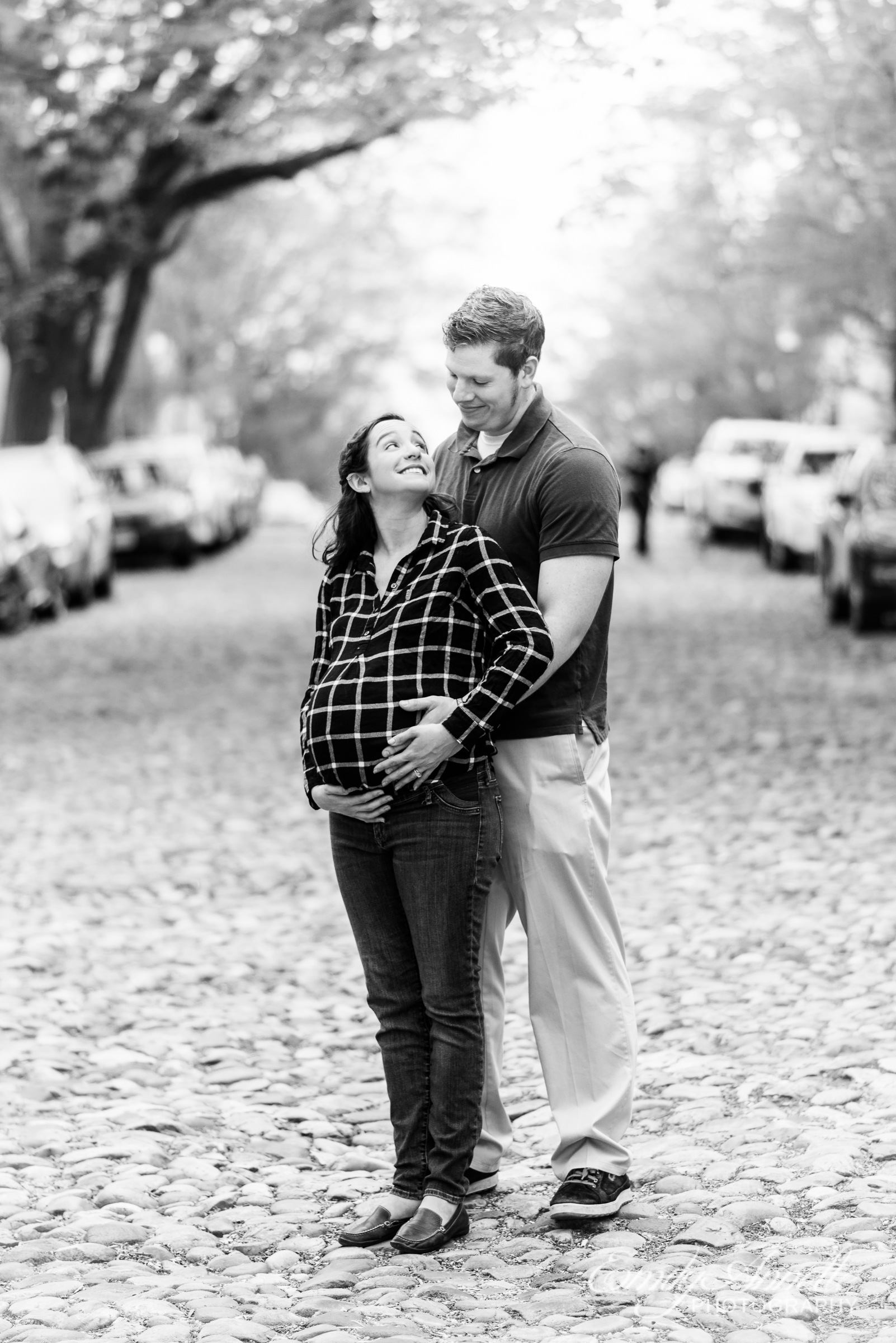 A pregnant woman poses with her husband for modern maternity photos on a cobblestone street in Old Town Alexandria wearing a fun casual shirt and jeans