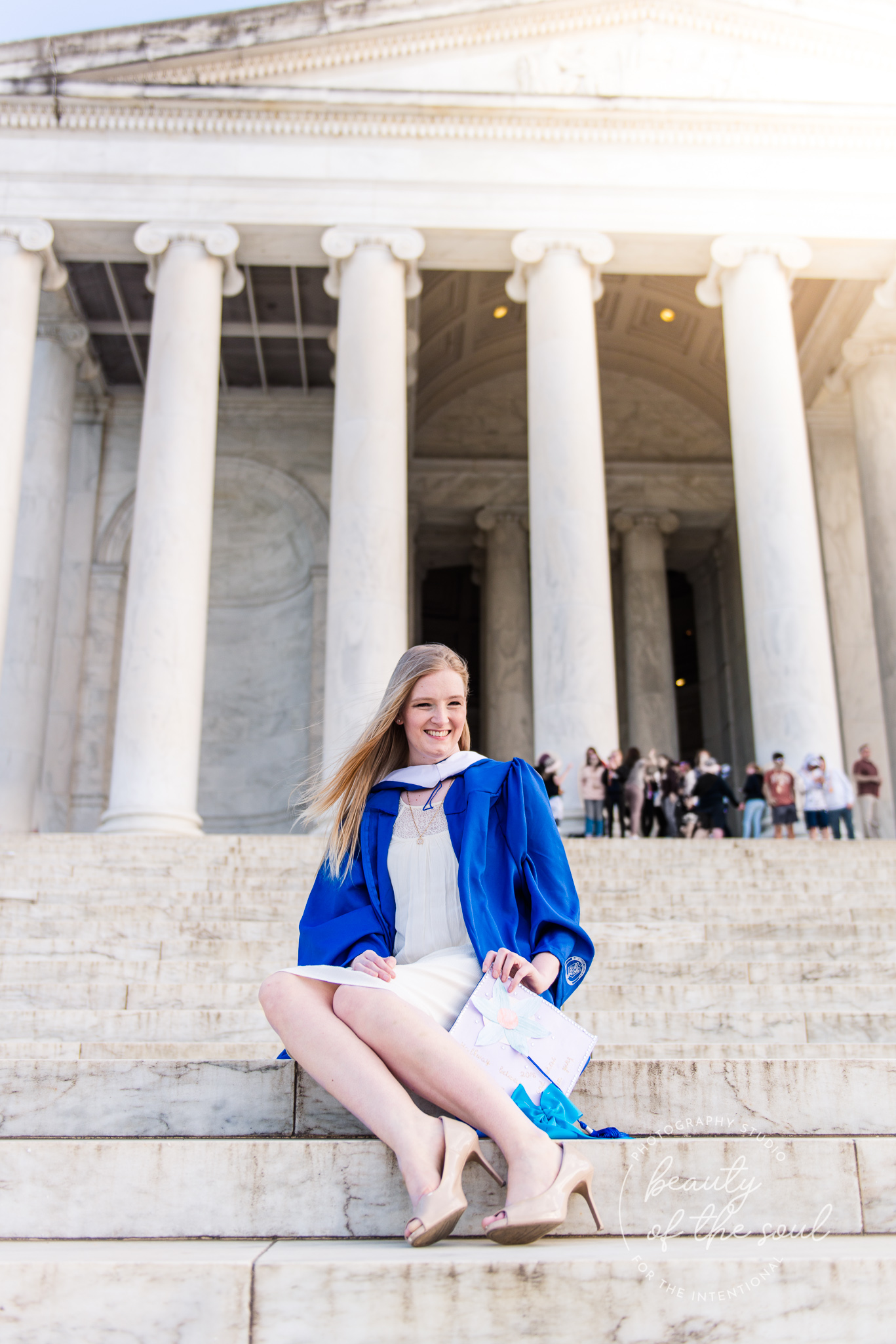 A college grad sits on the steps of the Jefferson Memorial for a Tidal Basin cap and gown session in Washington, DC before her graduation from Marymount University in Arlington, Northern Virginia