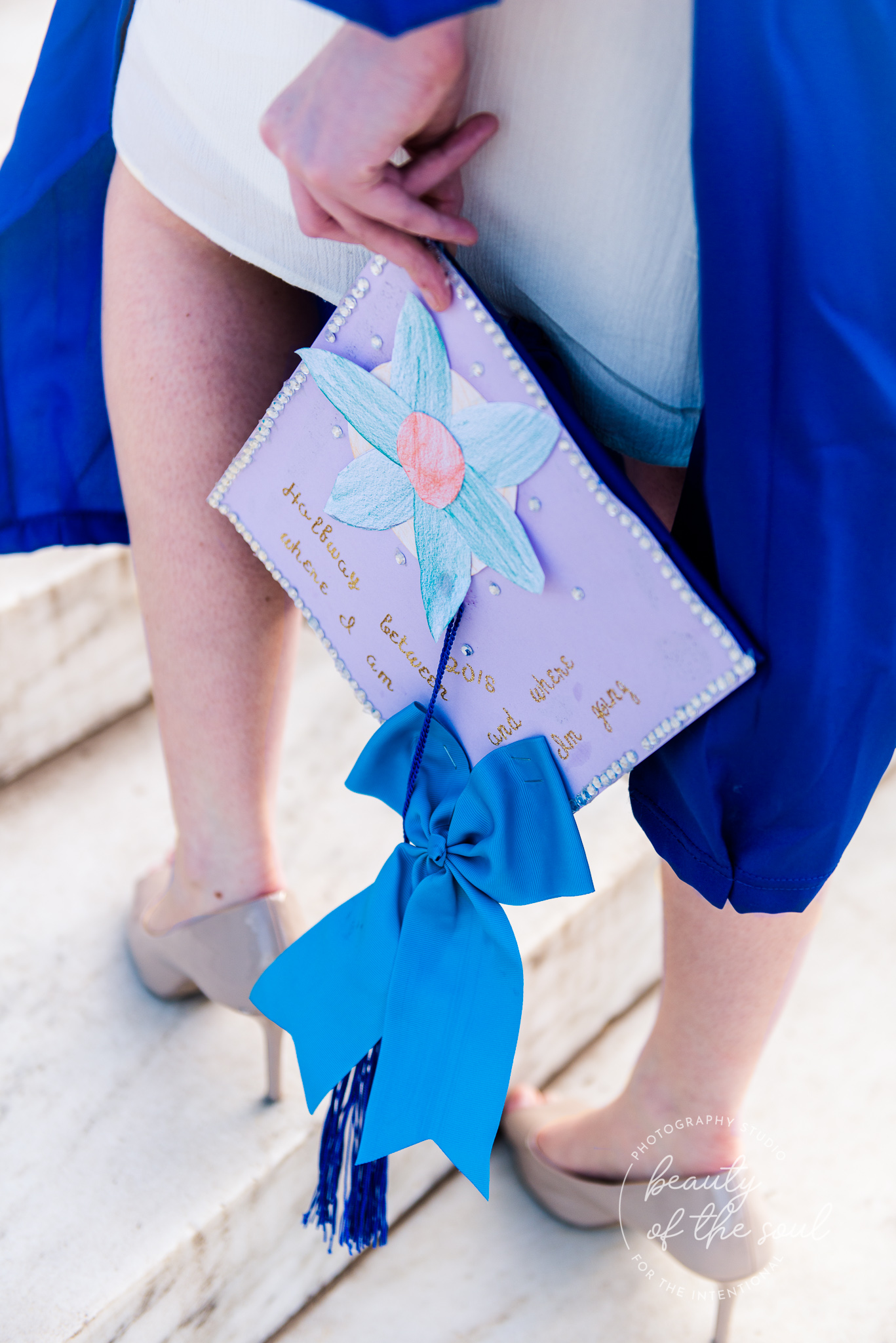 A college grad holds her decorated graduation cap walks up the steps of the Jefferson Memorial for a Tidal Basin cap and gown session in Washington, DC before her graduation from Marymount University in Arlington, Northern Virginia