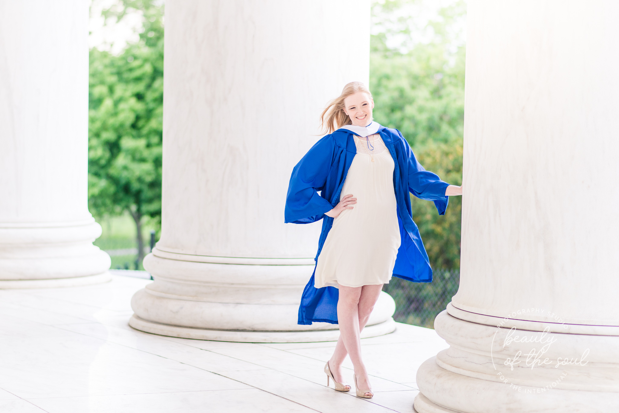 A college grad poses within the columns of the Jefferson Memorial for a Tidal Basin cap and gown session in Washington, DC before her graduation from Marymount University in Arlington, Northern Virginia