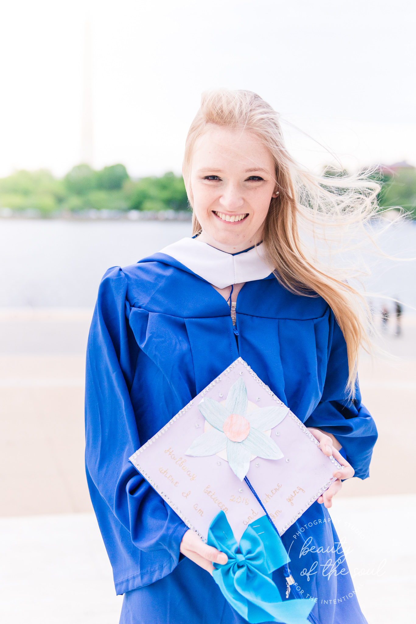 A college grad poses by the Potomac River for a Tidal Basin cap and gown session next to the Jefferson Memorial in Washington, DC before her graduation from Marymount University in Arlington, Northern Virginia