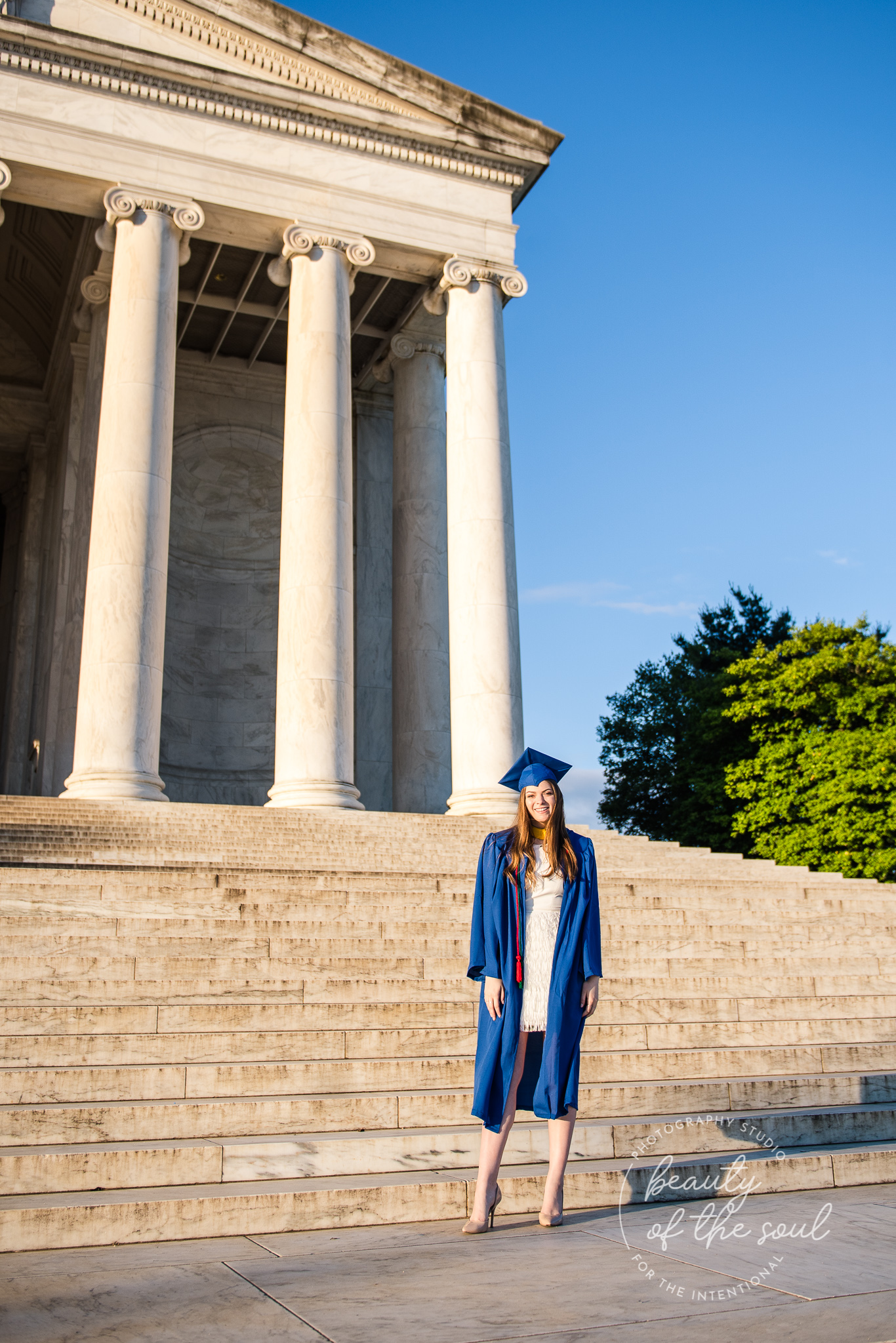 A graduate from Marymount University in Arlington, Northern Virginia standing on the steps of the Jefferson Memorial for her cap and gown session in Washington, DC