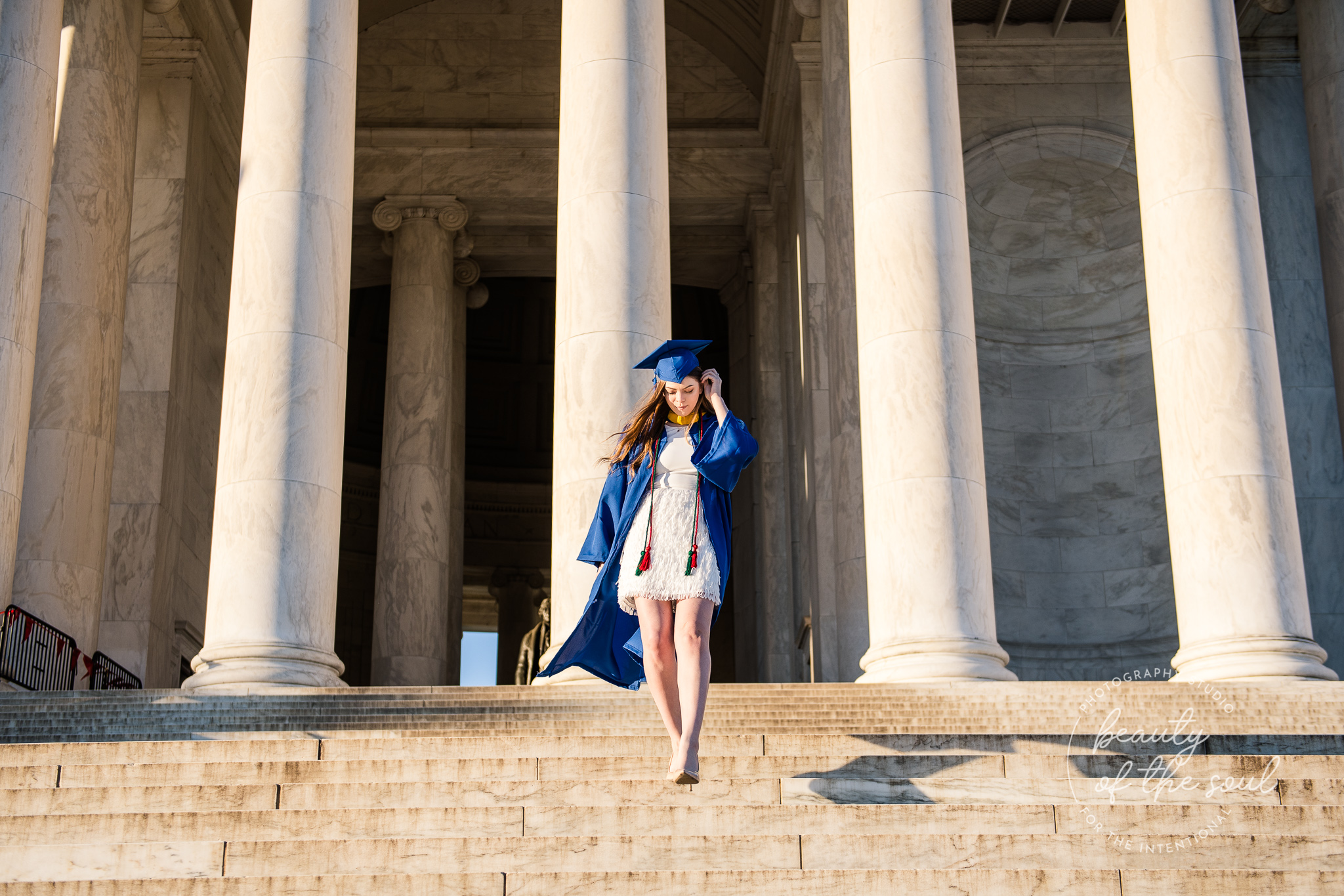 A graduate from Marymount University in Arlington, Northern Virginia walking down the steps of the Jefferson Memorial for her cap and gown session in Washington, DC