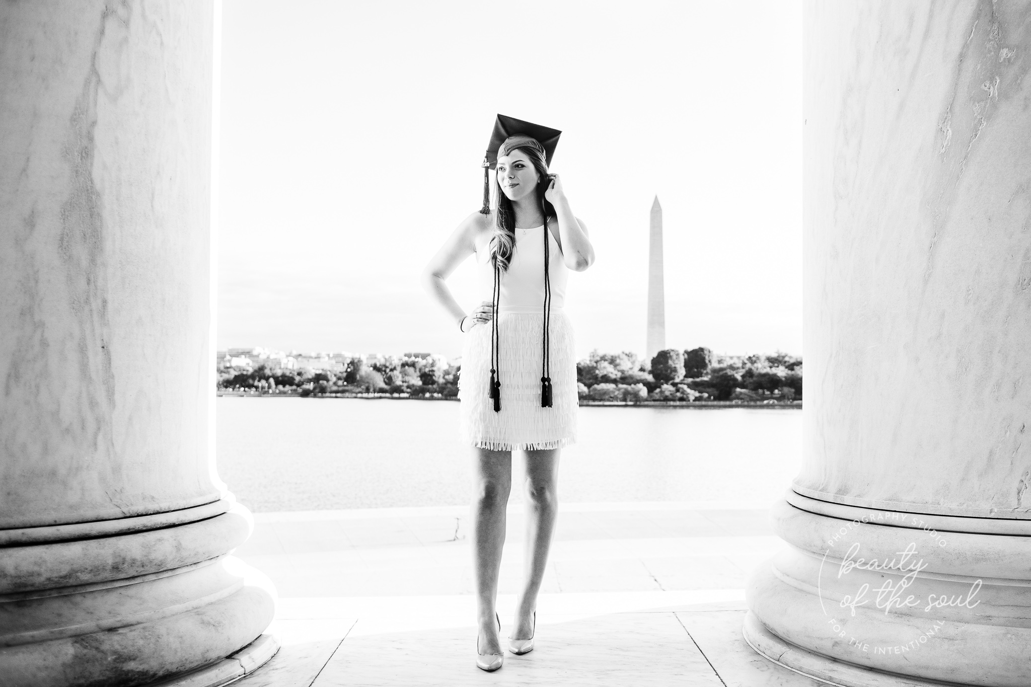 A graduate from Marymount University in Arlington, Northern Virginia standing in front of the Washington Monument at the Jefferson Memorial for her cap and gown session in Washington, DC