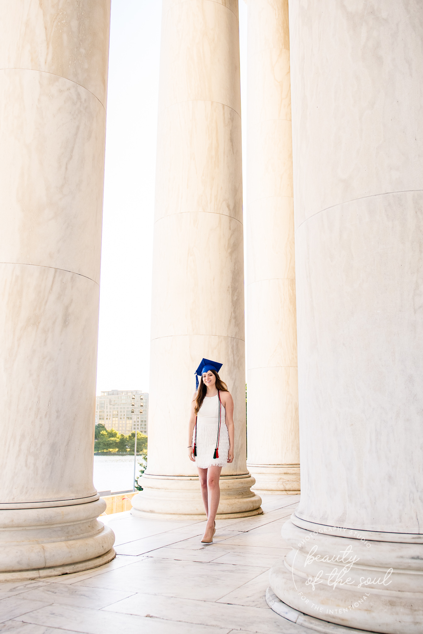 A graduate from Marymount University in Arlington, Northern Virginia walking in the Jefferson Memorial for her cap and gown session in Washington, DC