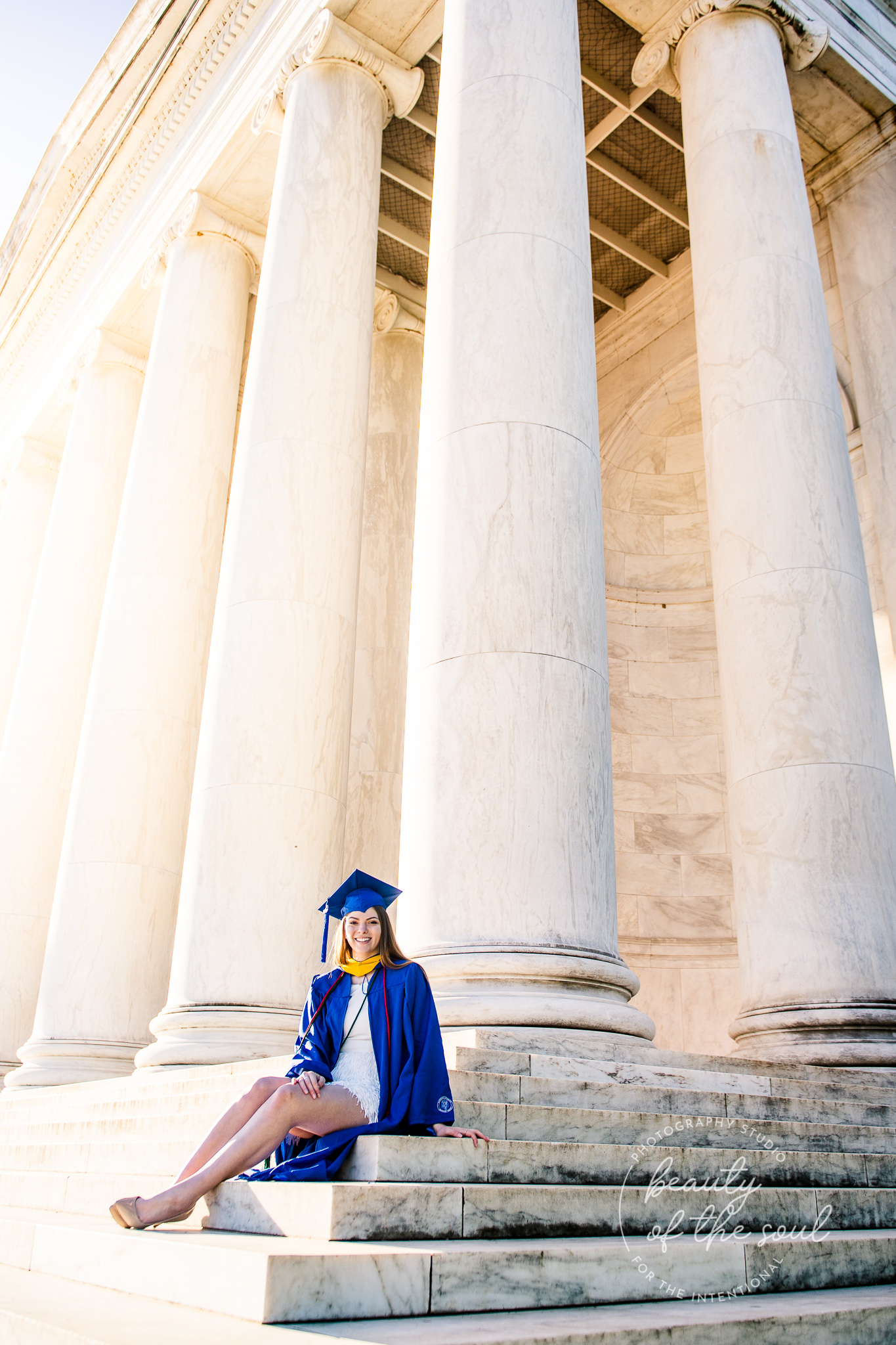 A graduate from Marymount University in Arlington, Northern Virginia sitting on the steps of the Jefferson Memorial for her cap and gown session in Washington, DC